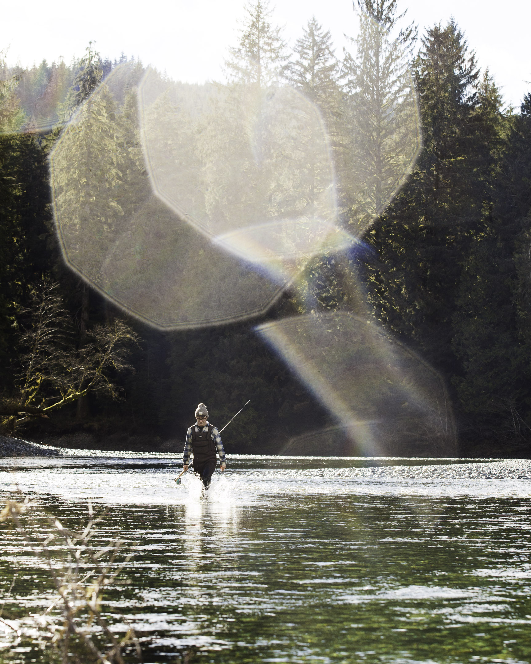 A fisherman walking up the Gordon River in Port Renfrew, BC, Canada