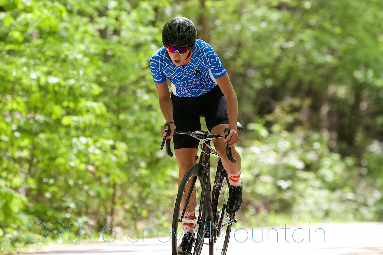 Daphne gets out of the saddle as she crests the climb.Photo by SnowyMountain Photography.