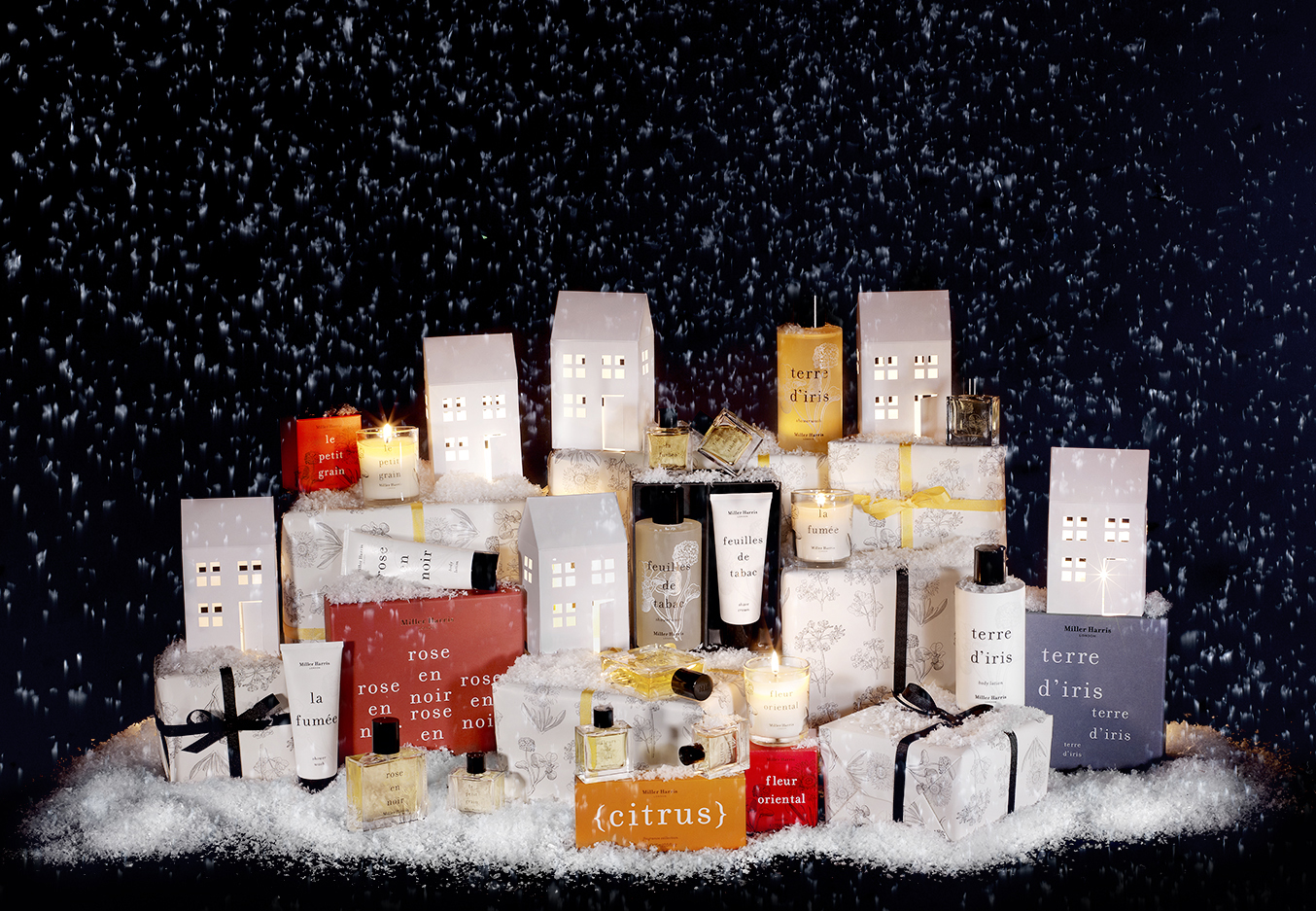 Perfumes and other cosmetics in a christmas still life setting with houses and snow, London product photographer chris howlett