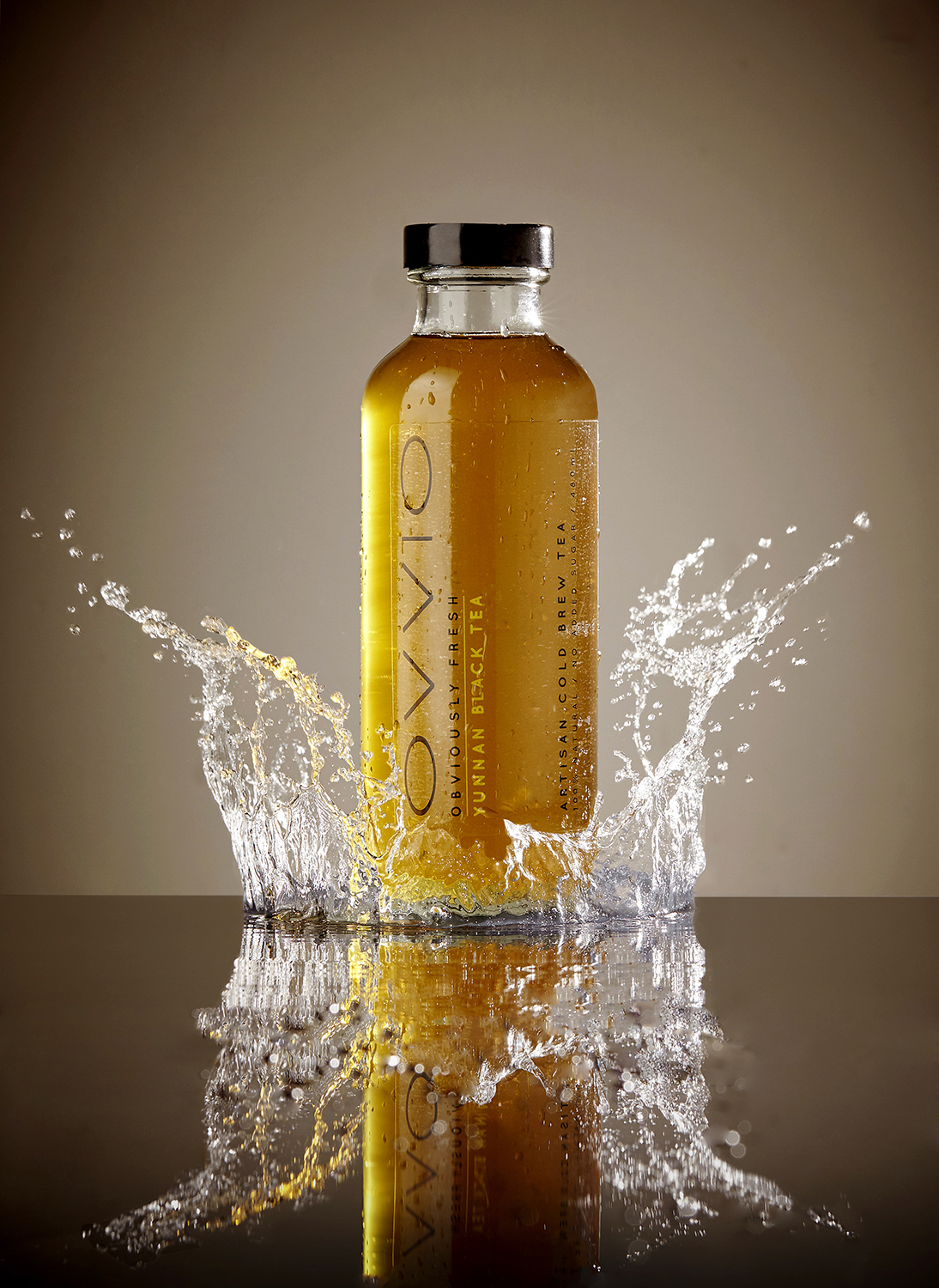 High speed water splash photography for advertising by London still life photographer. Drinks bottle in splash