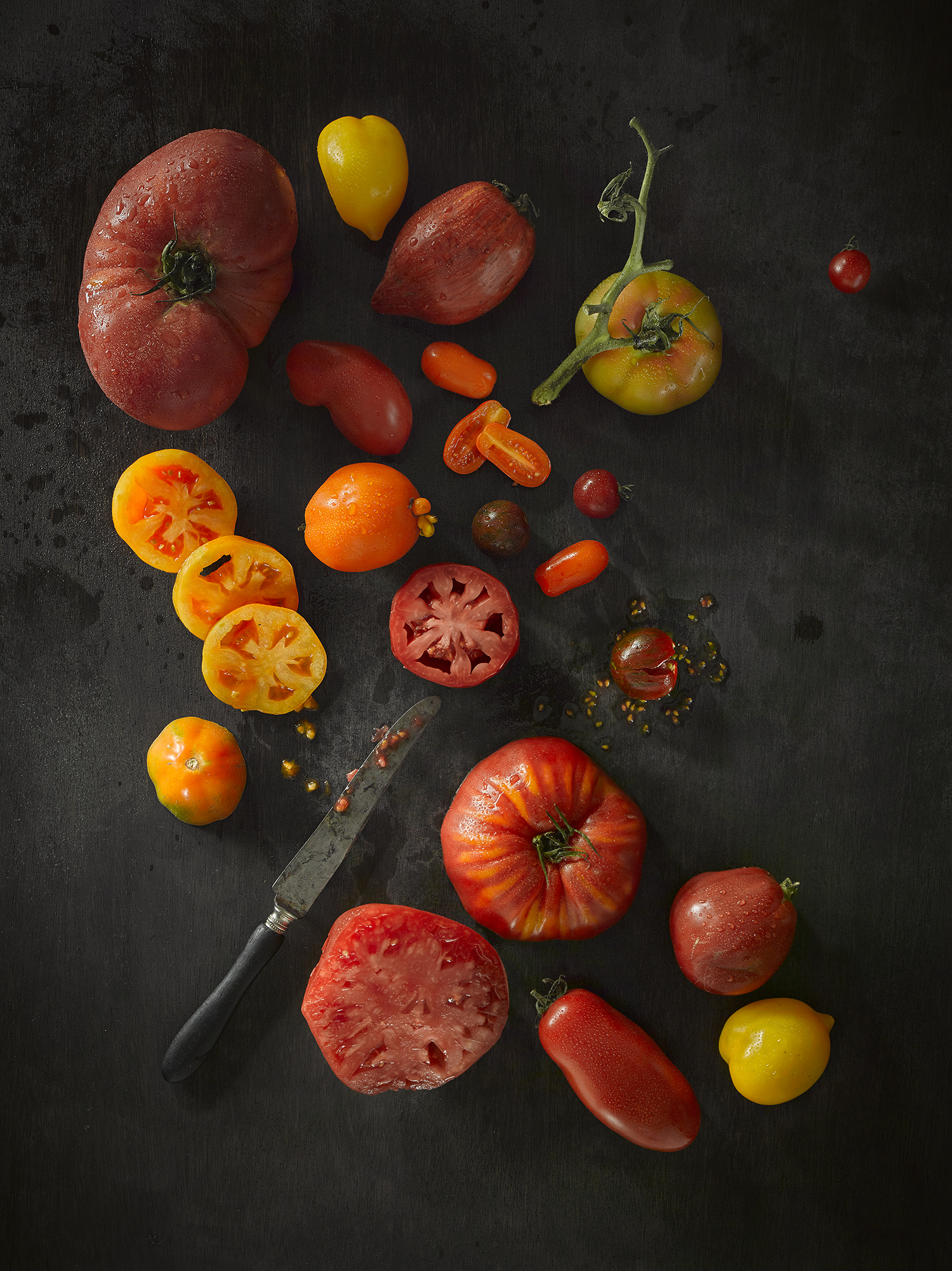 Food photography, mixed tomatoes create this still life food composition from advertising Croydon and London photographer chris howlett. The reds, yellows and ripeness of tomatoes look bright against dark wood.