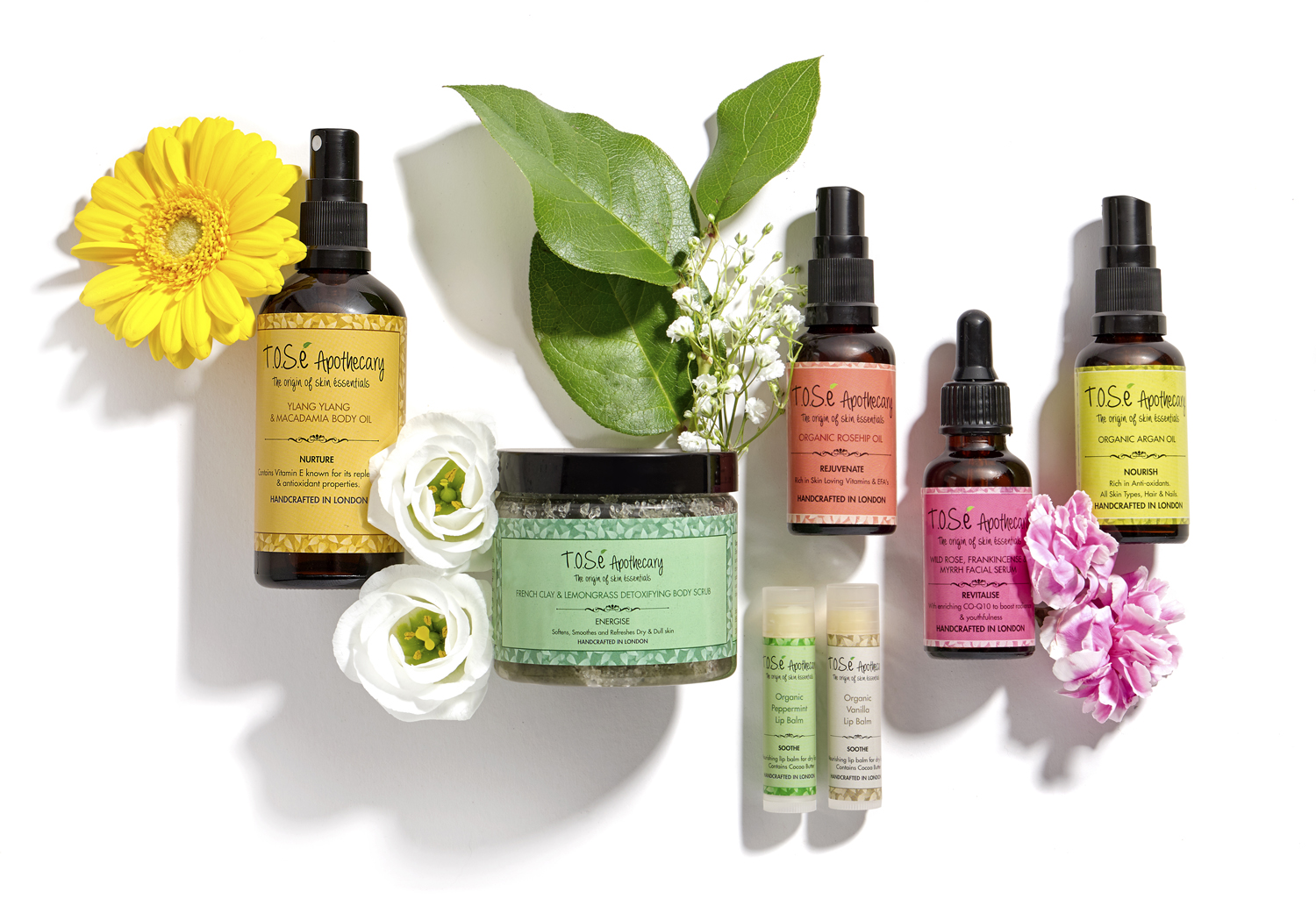 Beauty products, cosmetics make up in lifestyle image on white with flowers and fresh foliage around products, London still life product photographer