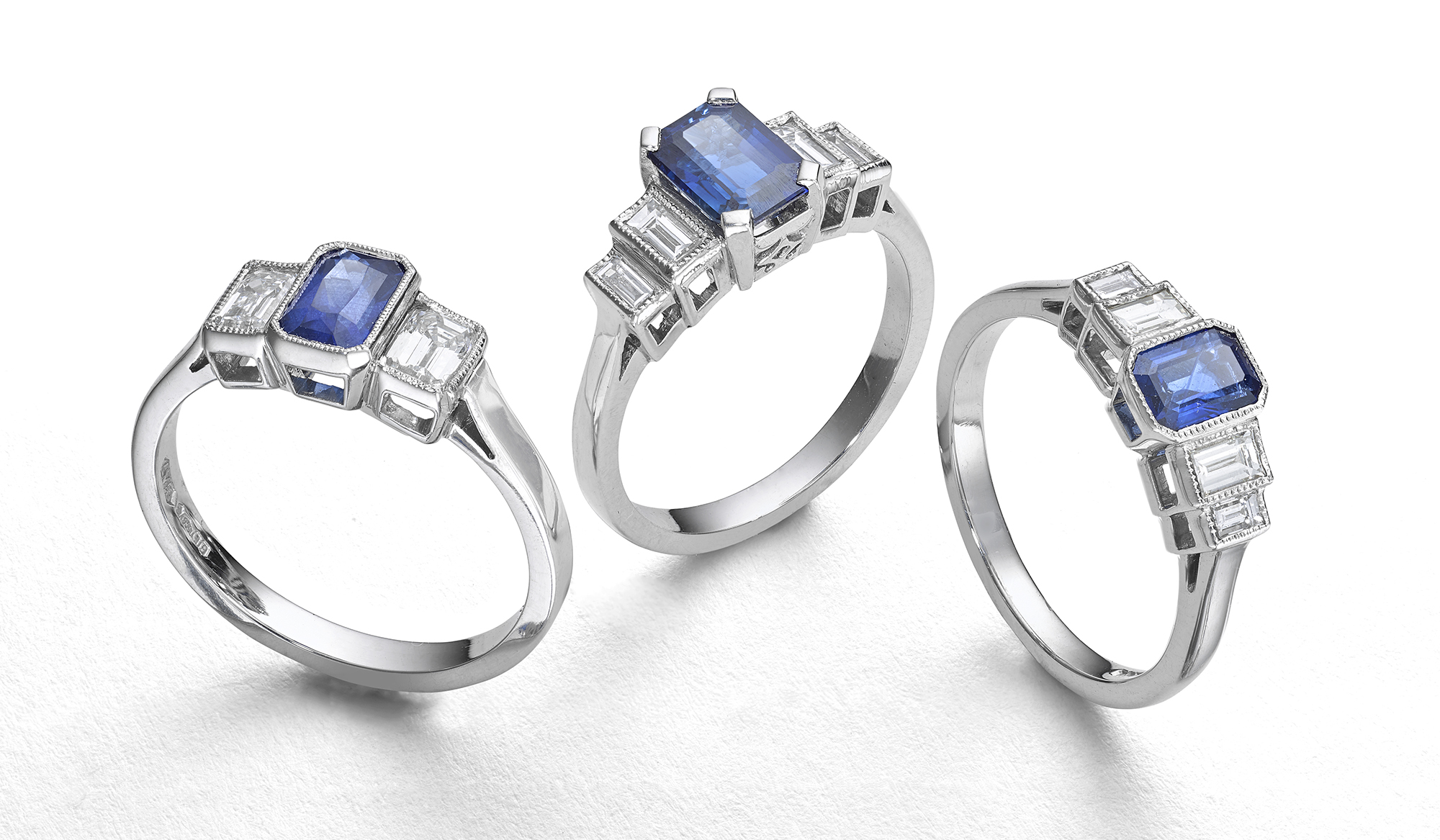 Creative still life jewellery photography, Set of three rings with soft shadow on white, blue saphires on silver rings, London jewellery photographer