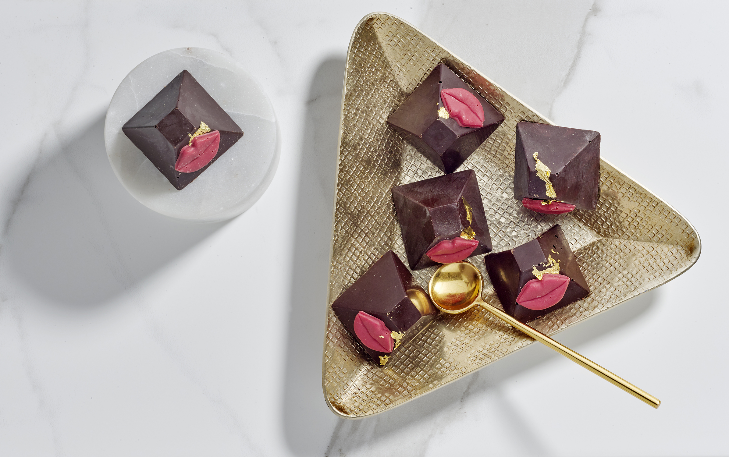 Creative food packshot photography, still life photography - individual chocolate pieces on luxury background product photography in London