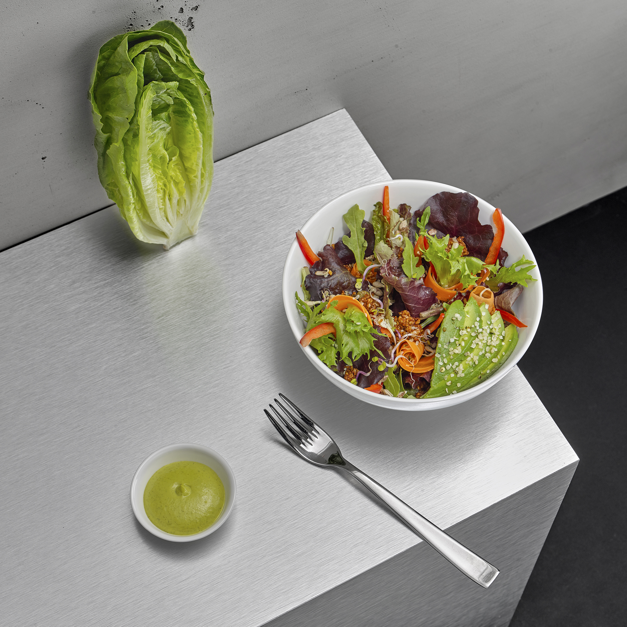Still life food and drink photographer. A salad with fork, location photography industrial style restaurant in London. Howlett Photography