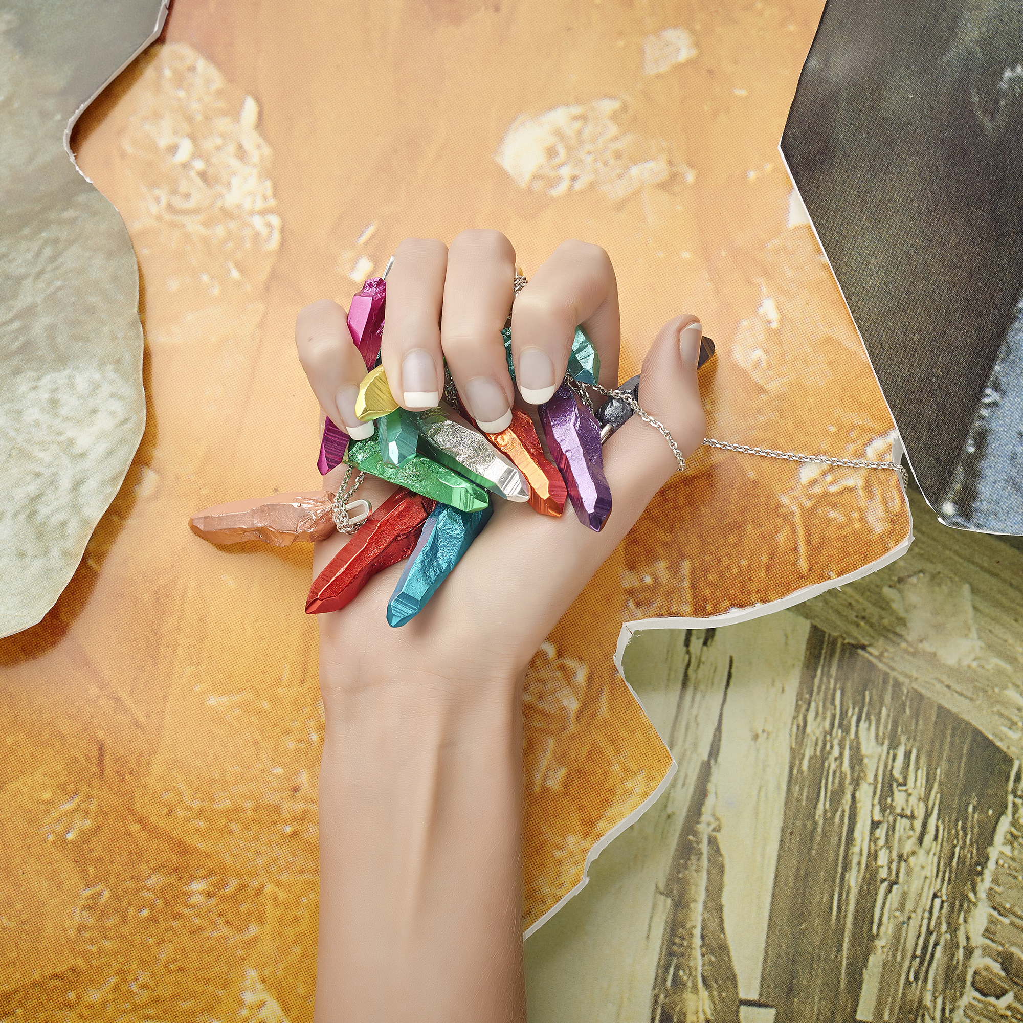 hand model clasping selection of pendant jewellery on colourful vibrant creative still life background, product photography by chris howlett in london