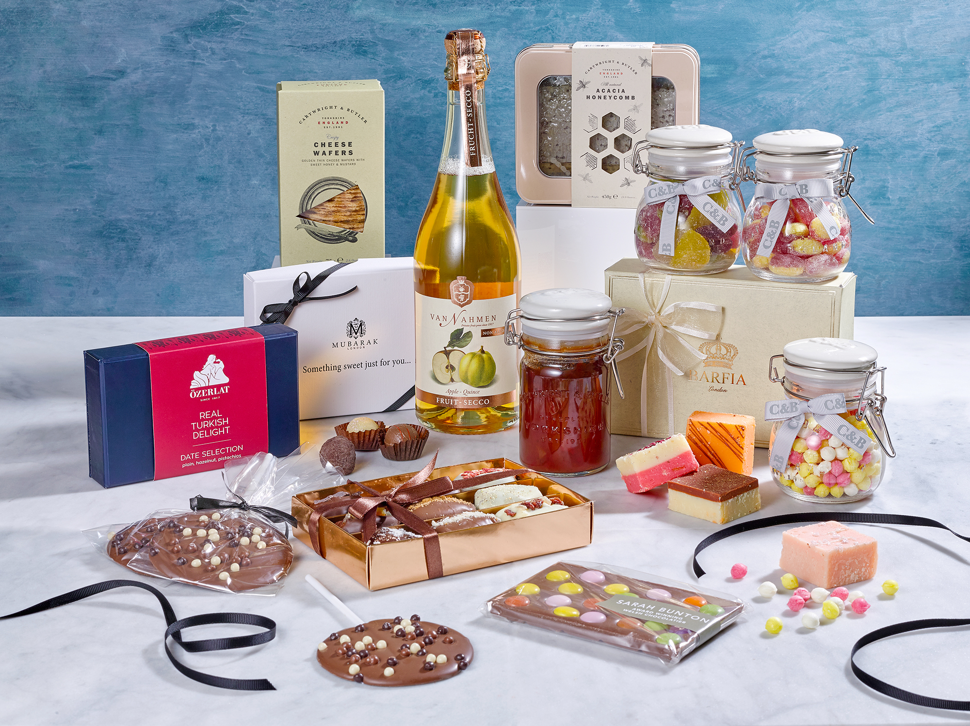 Food photography hampers, a collection of sweets chocolates fudges and other food and drink. This still life image was used for product packshots shot in London by Chris Howlett