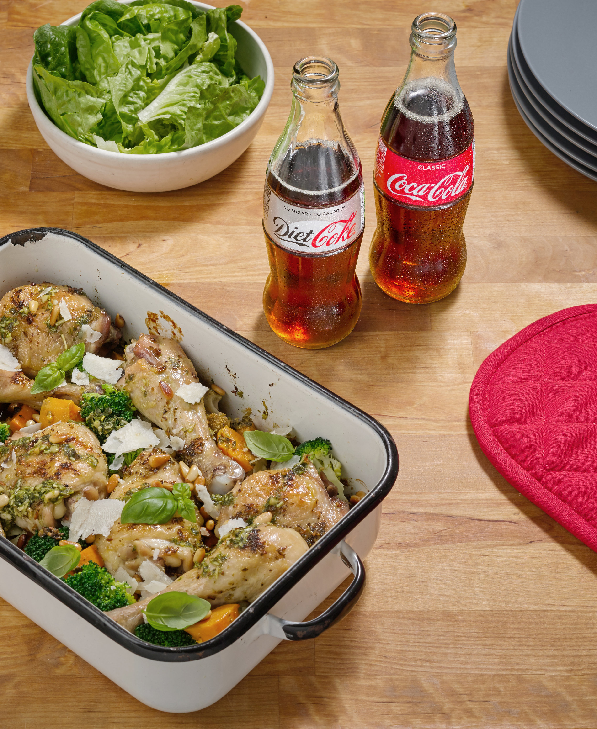 Chicken bake accompany 2 bottles of coke product. Typical food adveetising still photograph with props creativly placed around drink