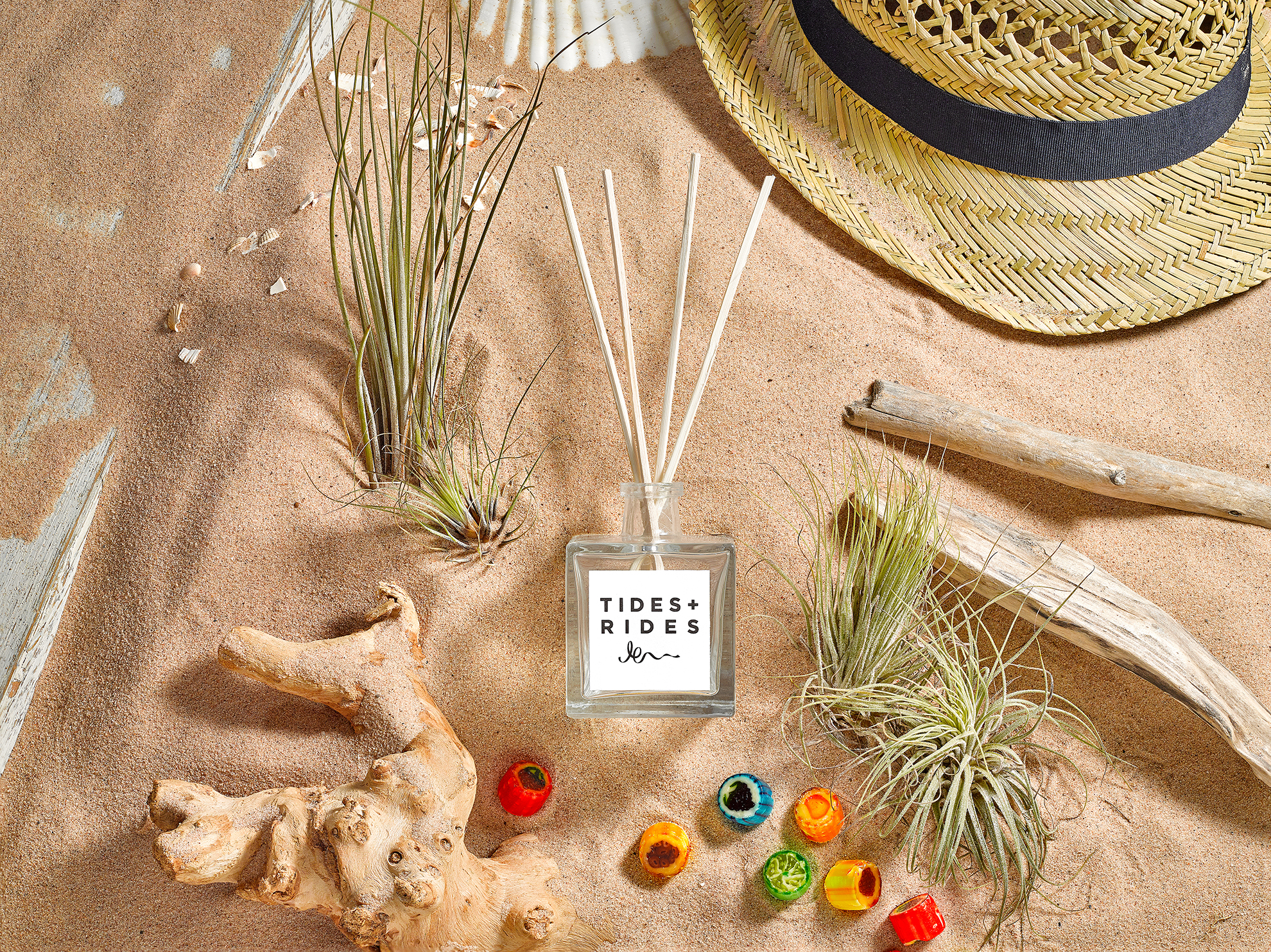 sand sea and grasses make up this lifestyle creative advertising product photo. Created in product packshot studio by Howlett photography