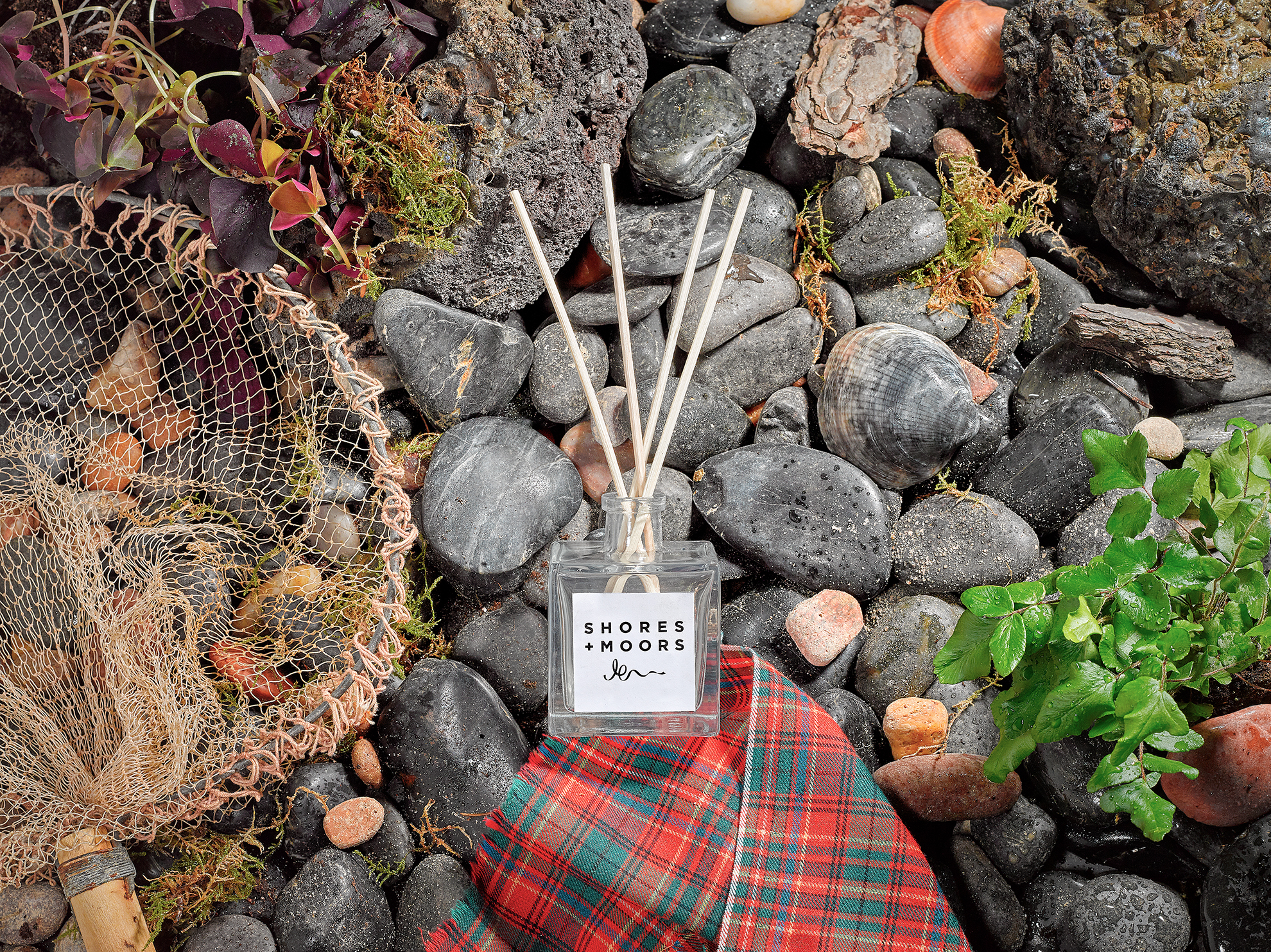 Scottish costal still life scene with tartan patten fishing nets pebbles and sea grasses. Lifestyle product photography from chris howlett