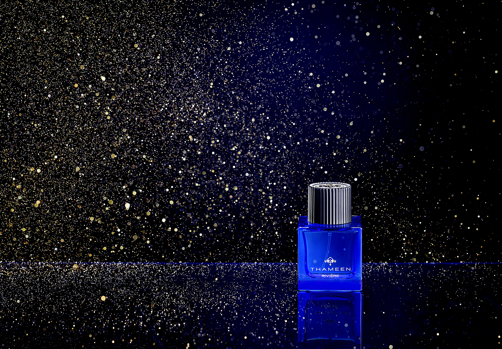 Advertising product photography, creative cosmetic perfume product with gold glitter explosion. Shot in London still life photography studio by Howlett photography