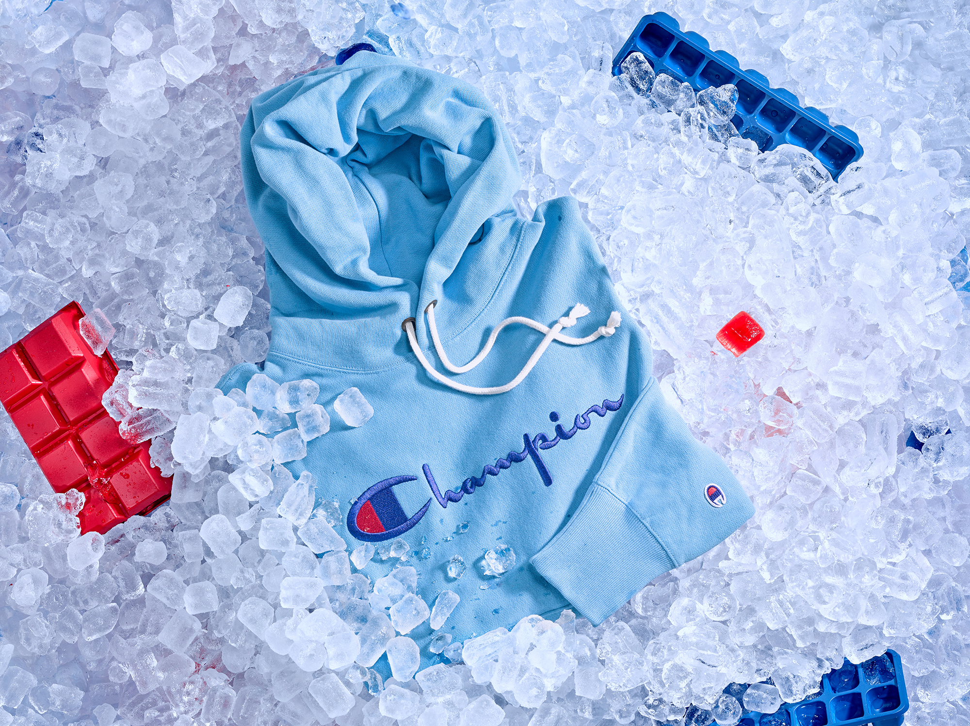 still life fashion accessories styled with ice cubes and ice trays, a blue hooded jumper partly submerged into the ice, product photography from london advertising photographer chris howlett