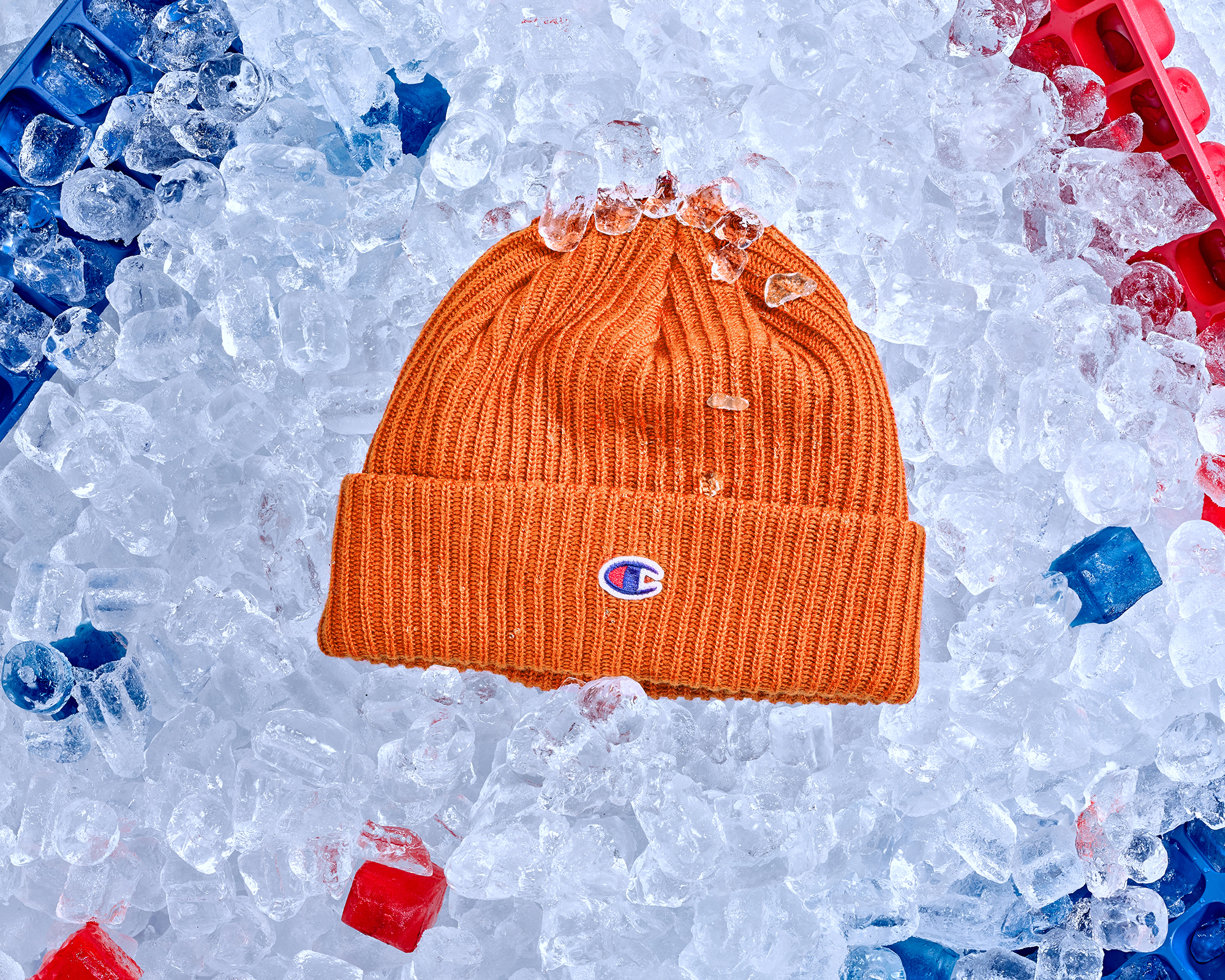 Orange beanie hat creative still life photography using fashion products shot overhead with creative props that surround the product