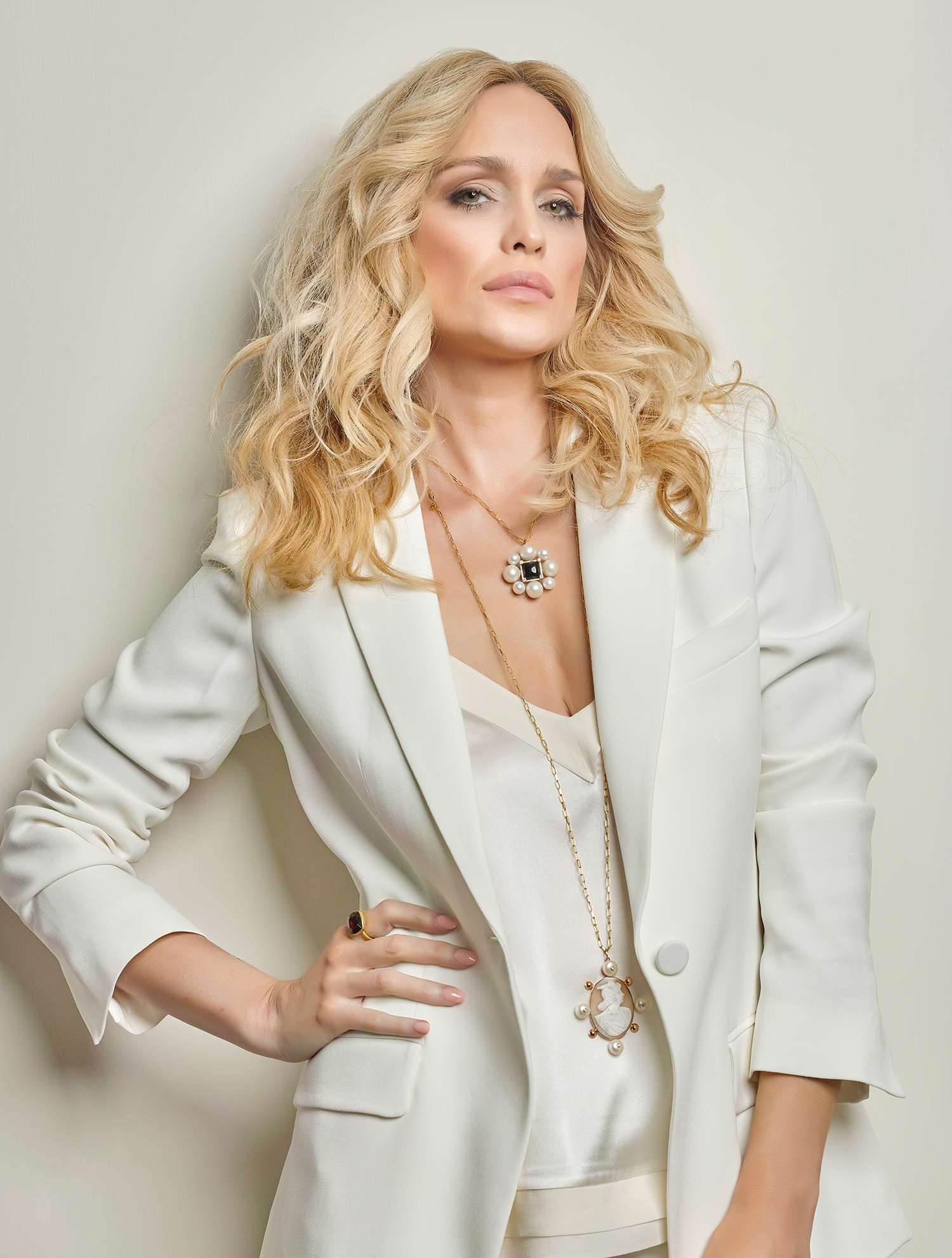 Jewellery on blond hair model hand on hip with large gold ring on finger, model looking at camera with large statement pendant around neck