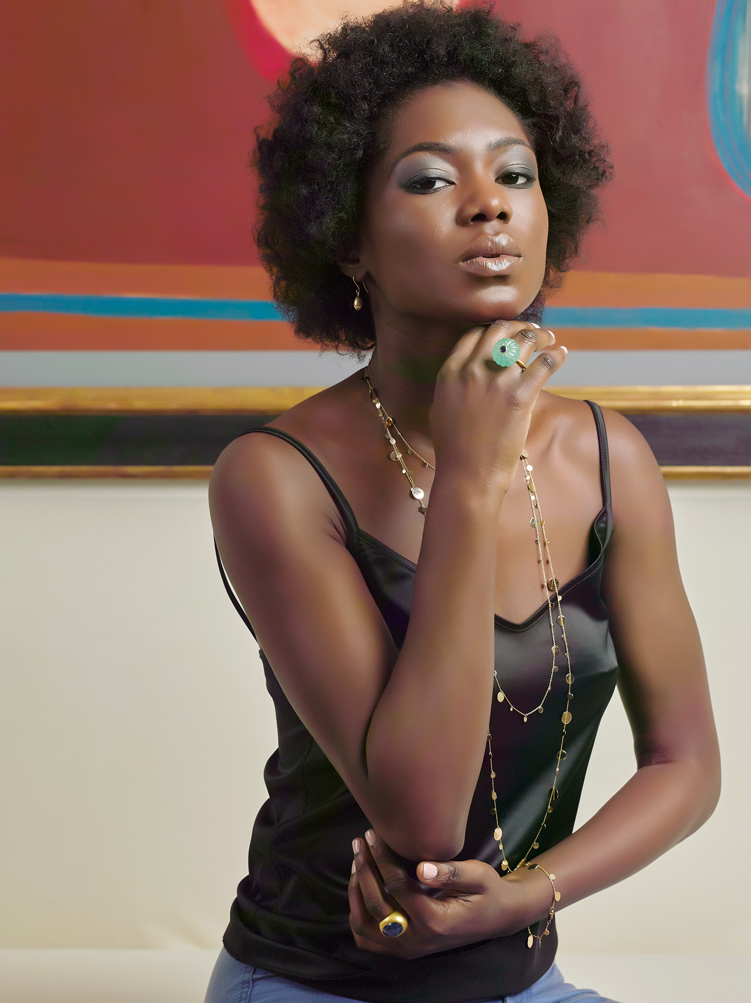Sixties look to this jewellery on model shot. Black model wearing long gold chain and large ring, looking straight at the photographer