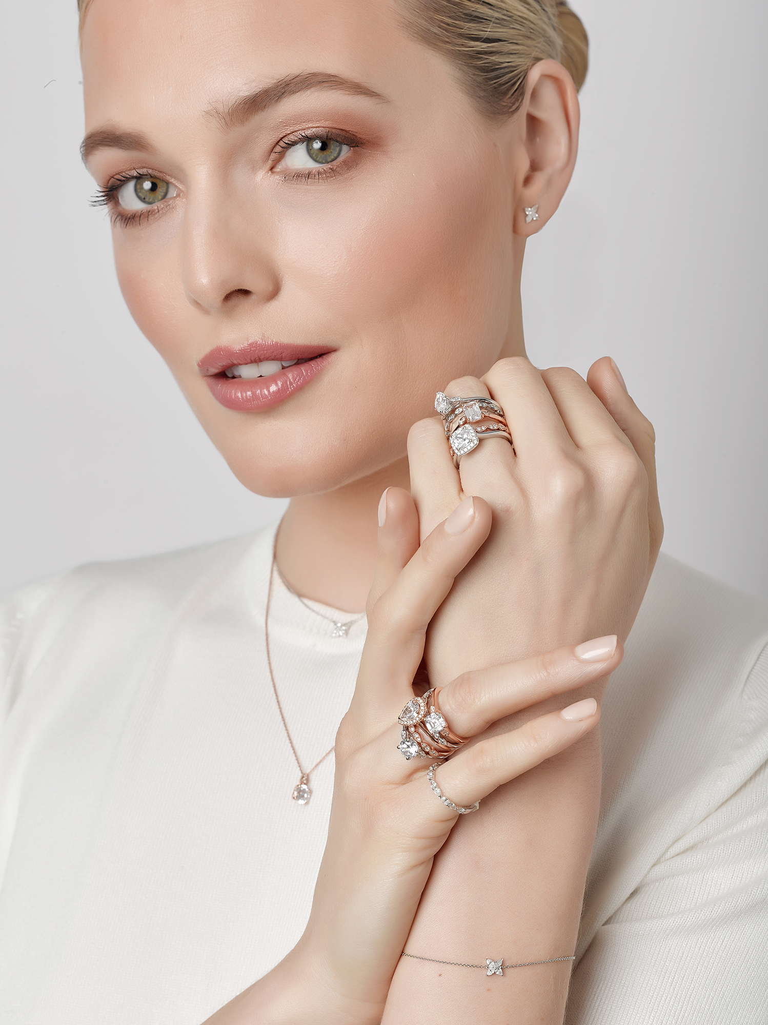 model wearing jewellery with white top and soft focused lighting hand together and model looking at camera.. Created in london jewellery photographic studio