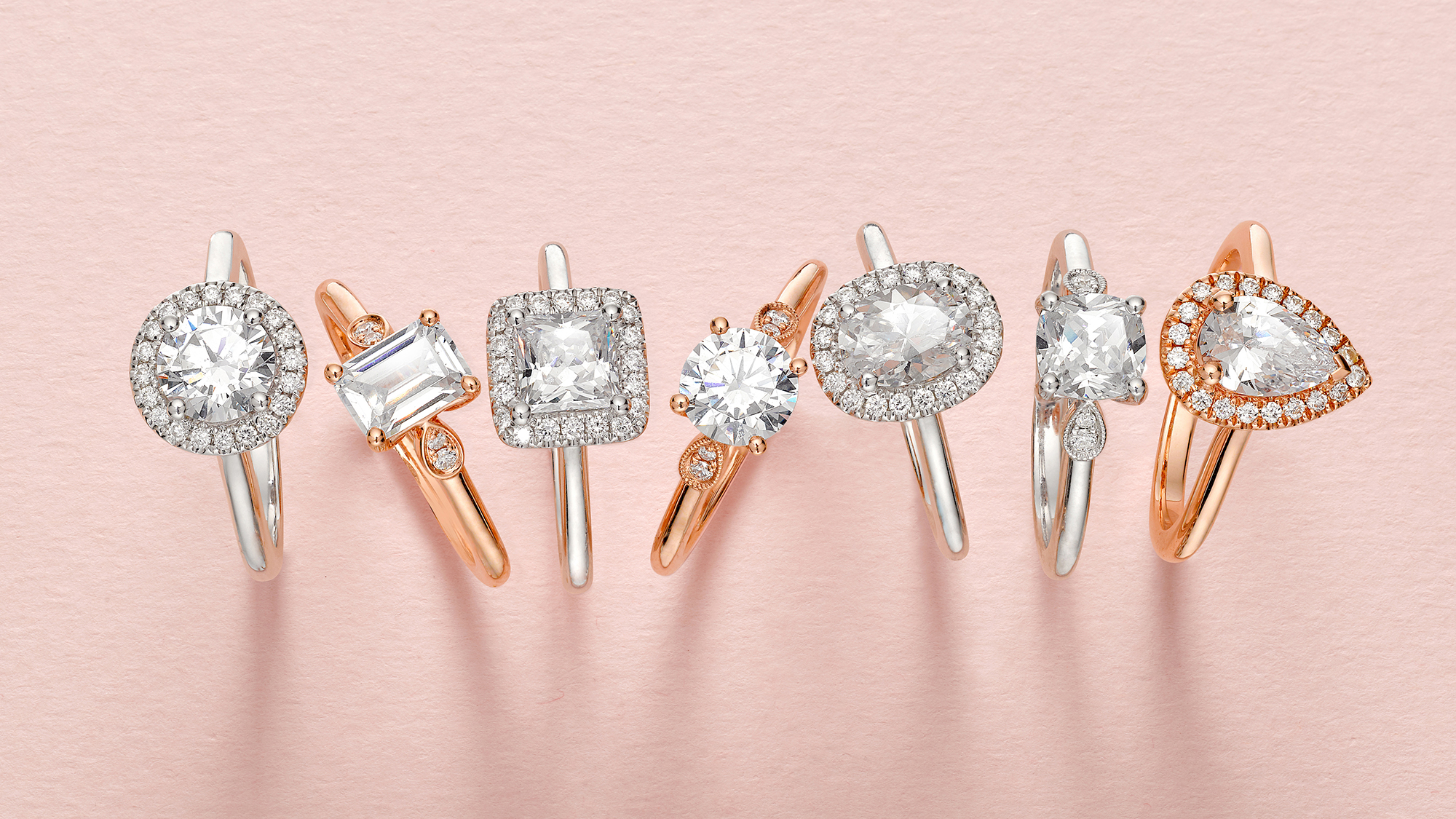 diamond engagements rings in long line with sparkling diamonds and polished golds, in pink gold and silver, shot in london jewellery photographic studio by chris howlett