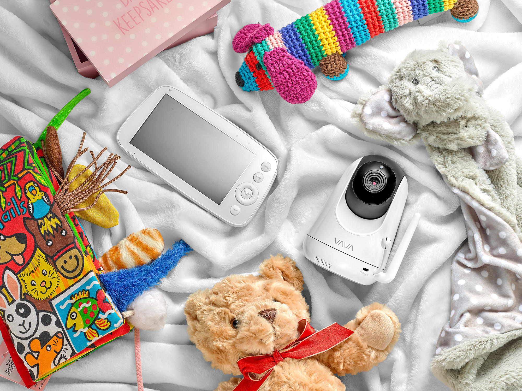 lifestyle product photography. Baby monitor and camera surrounded by lifestyle baby products on soft blanket. Created in London still life studio by chris howlett