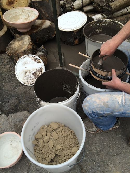Persuading a suspension of washed ash through an 80 mesh sieve. A bucket of washed, sieved and dried oak ash, ready for use, can be seen in the foreground (just turned out of the biscuit fired bowl, top left, used for drying).