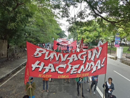 """hundreds of Luisita farm workers march to the RCBC compound inside Hacienda Luisita in Tarlac City to serve their """"notice of eviction."""" (Photo by UMA)"""