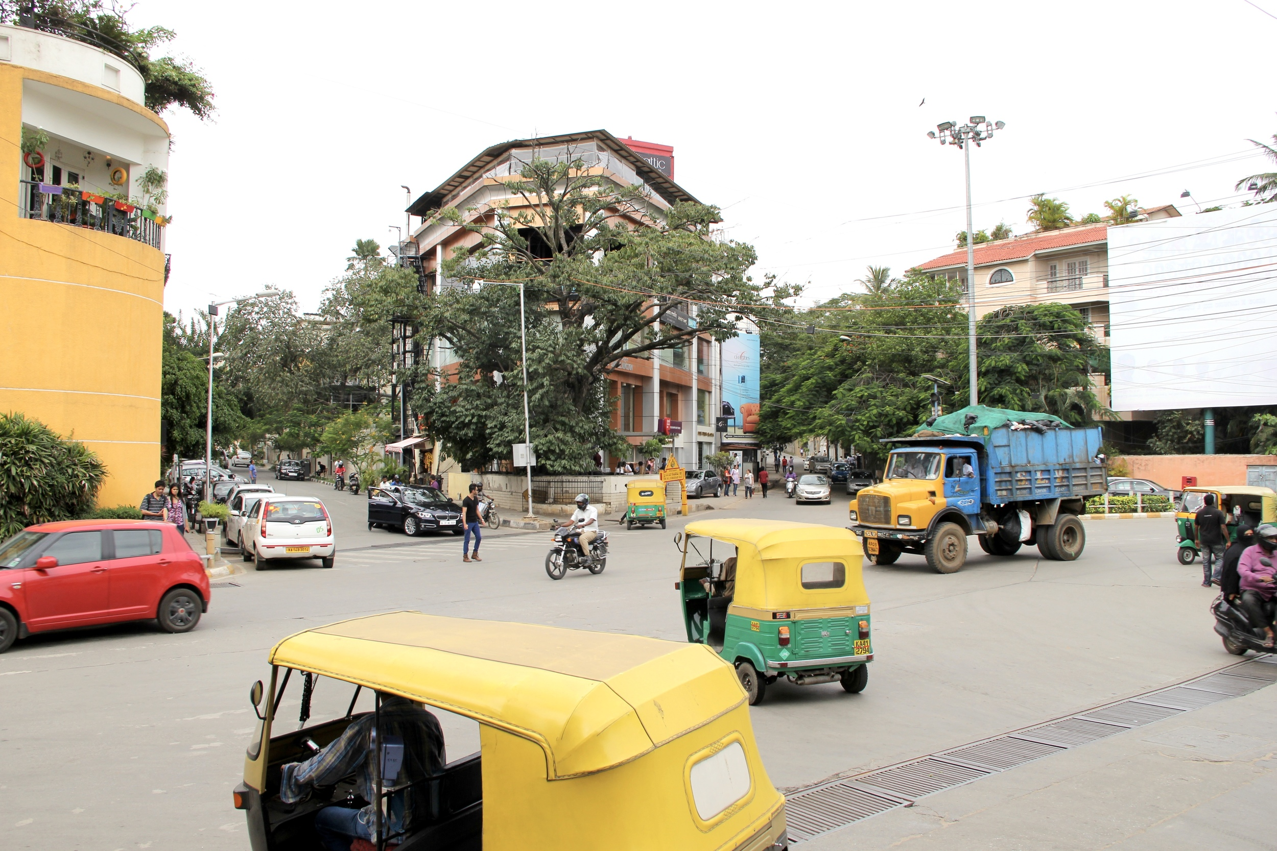 rickshaws criss cross an intersection in bangalore, india | beyond ordinary guides