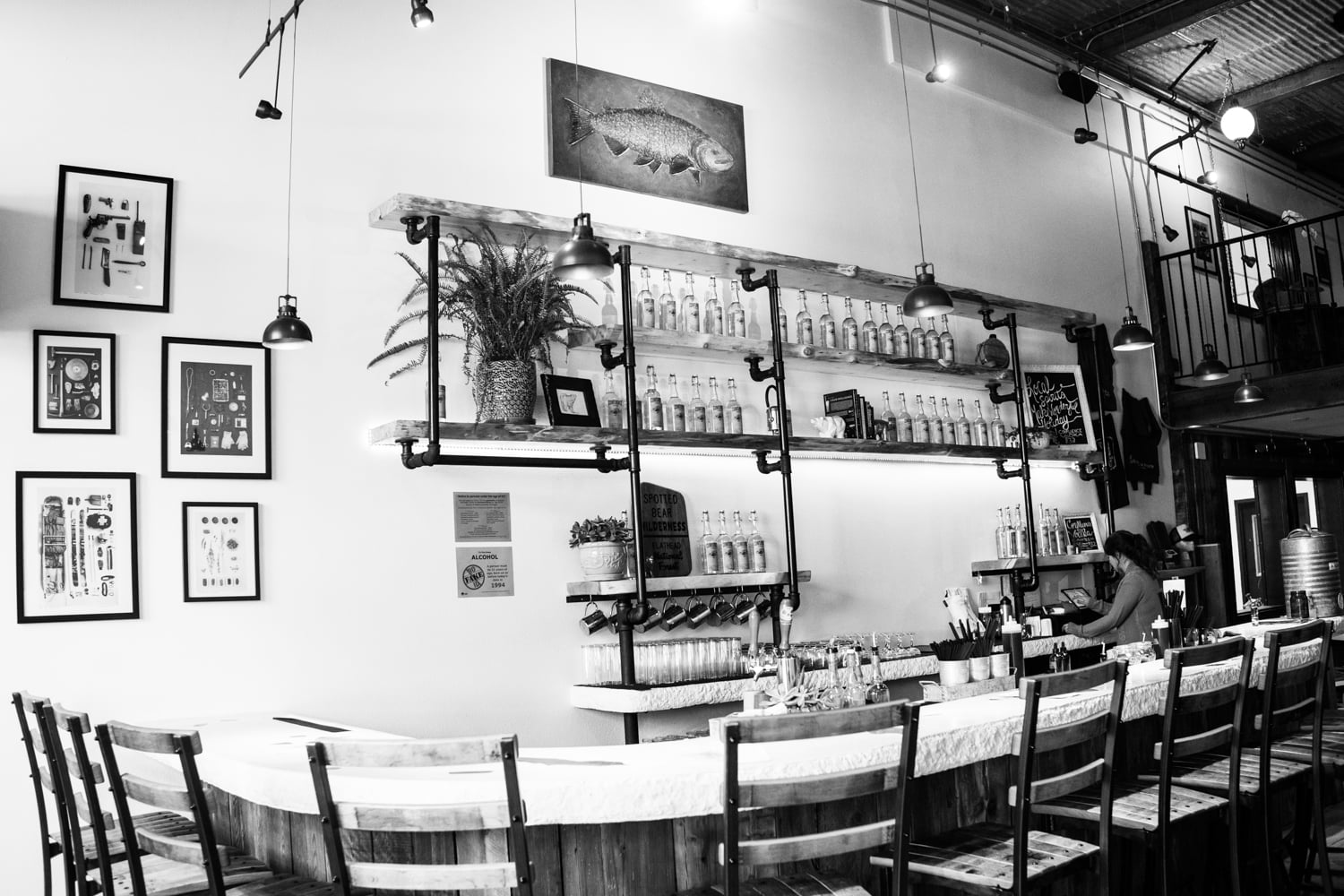 The new Spotted Bear Spirits Distillery in Whitefish, Montana. Featuring a vintage rustic wilderness decor and highlighting the art of Mandy Mohler, Field Guide Designs