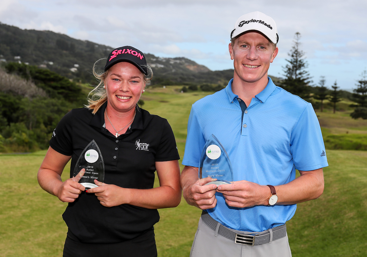 Brittney Dryland and James Anstiss pose with their trophies following their wins at the Muriwai Open in Auckland.