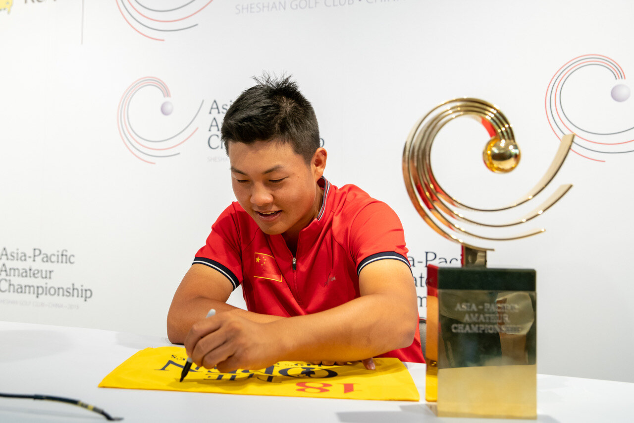 Yuxin Lin with his Asia-Pacific Amateur trophy at his side.