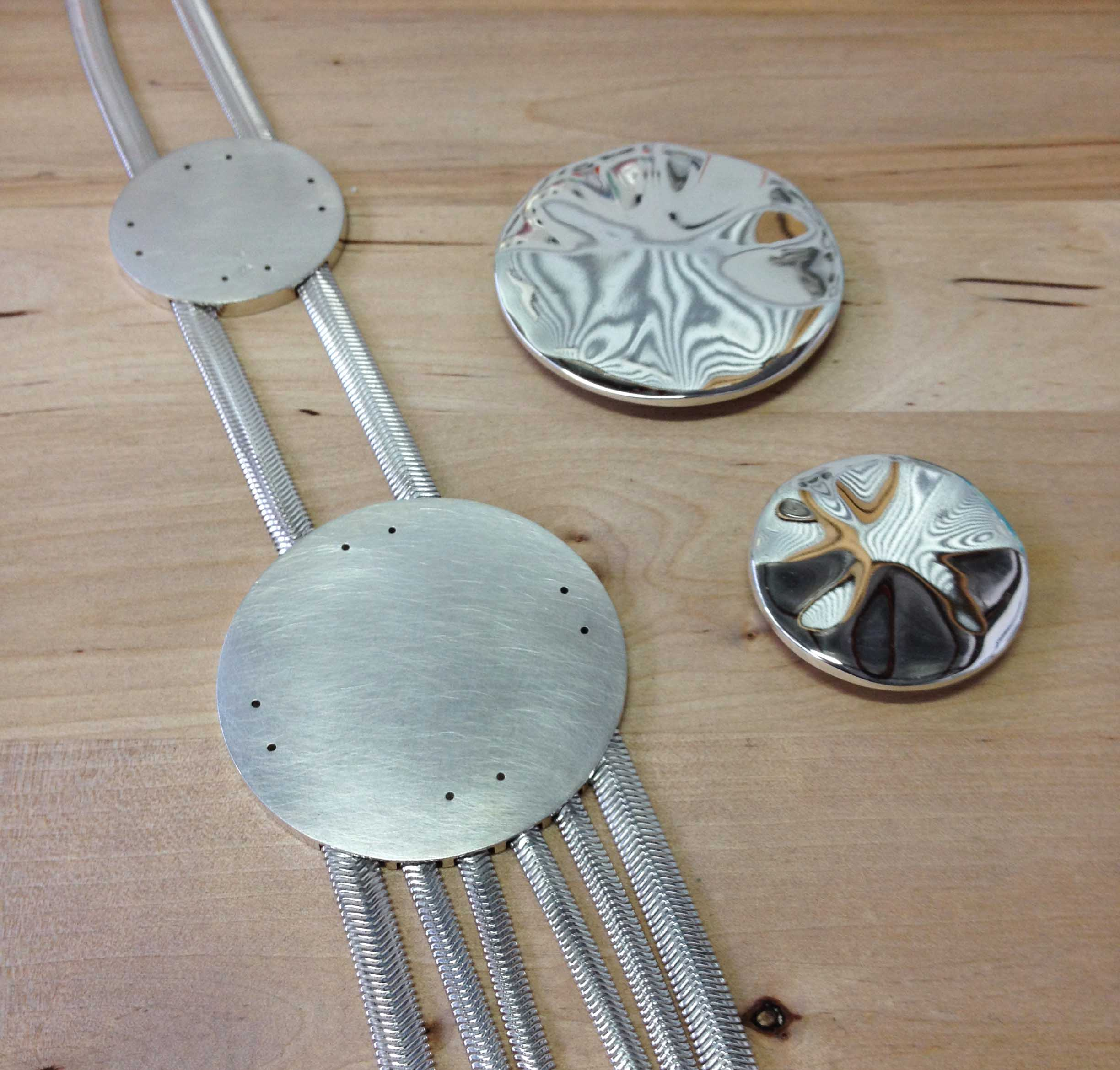 The necklace is all ready to be riveted. I decided to give the backing plates a brushed finish for a bit of contrast against the shiny chain and feature disks.