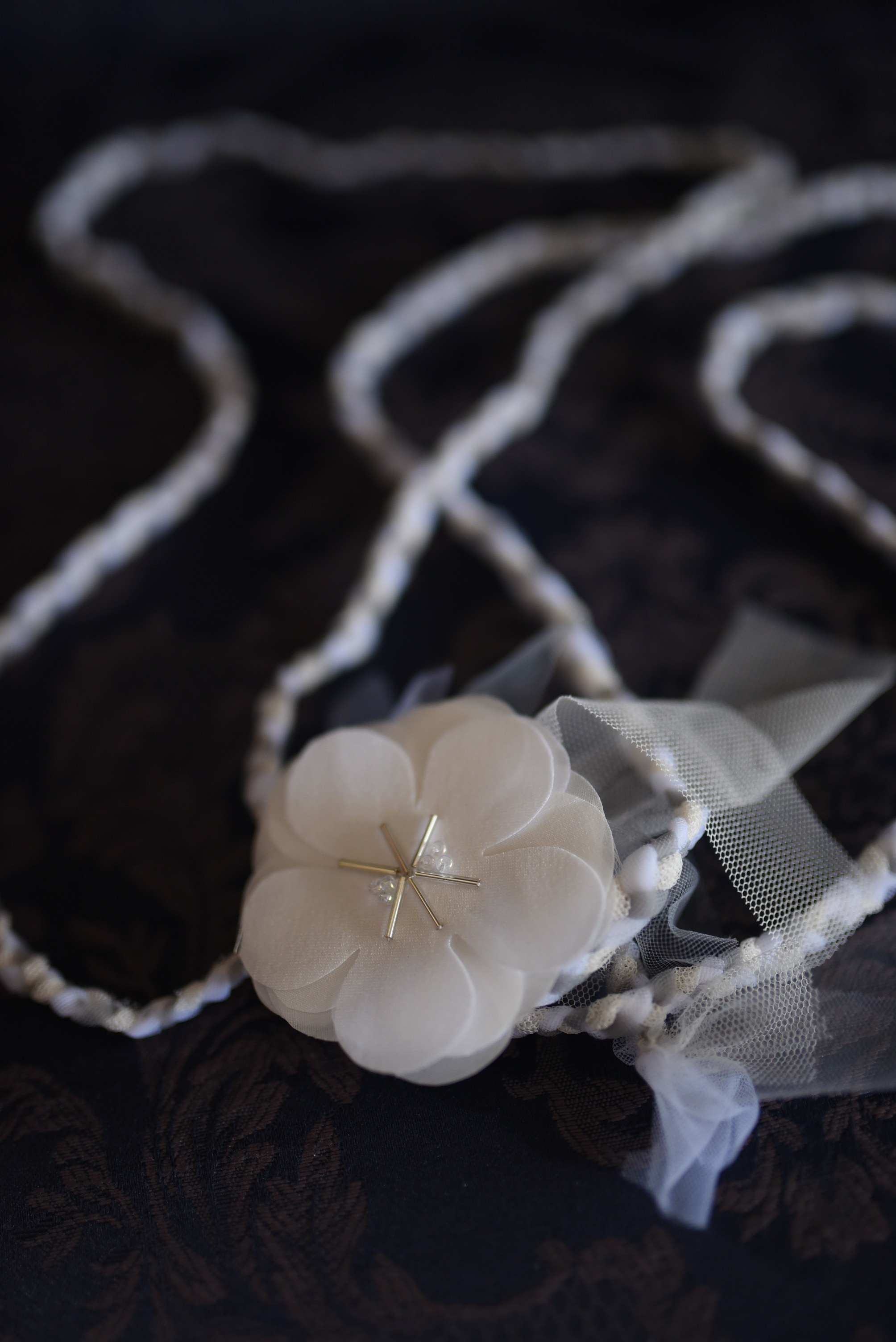 Our cord. Made by braided stretch tulle, in cream, gray, and white. With fabric flowers.