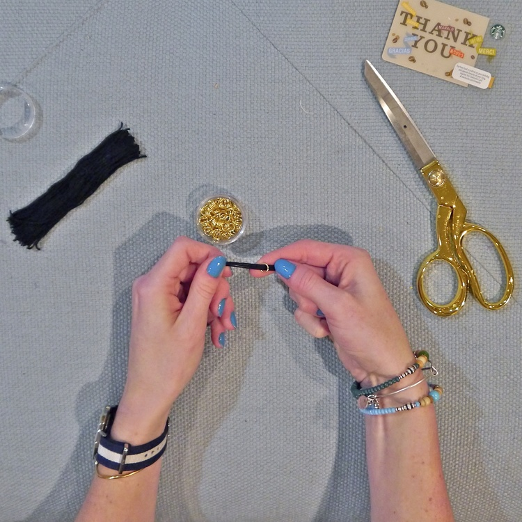 Take the folded thread you set aside and thread it through one of your jump beads.