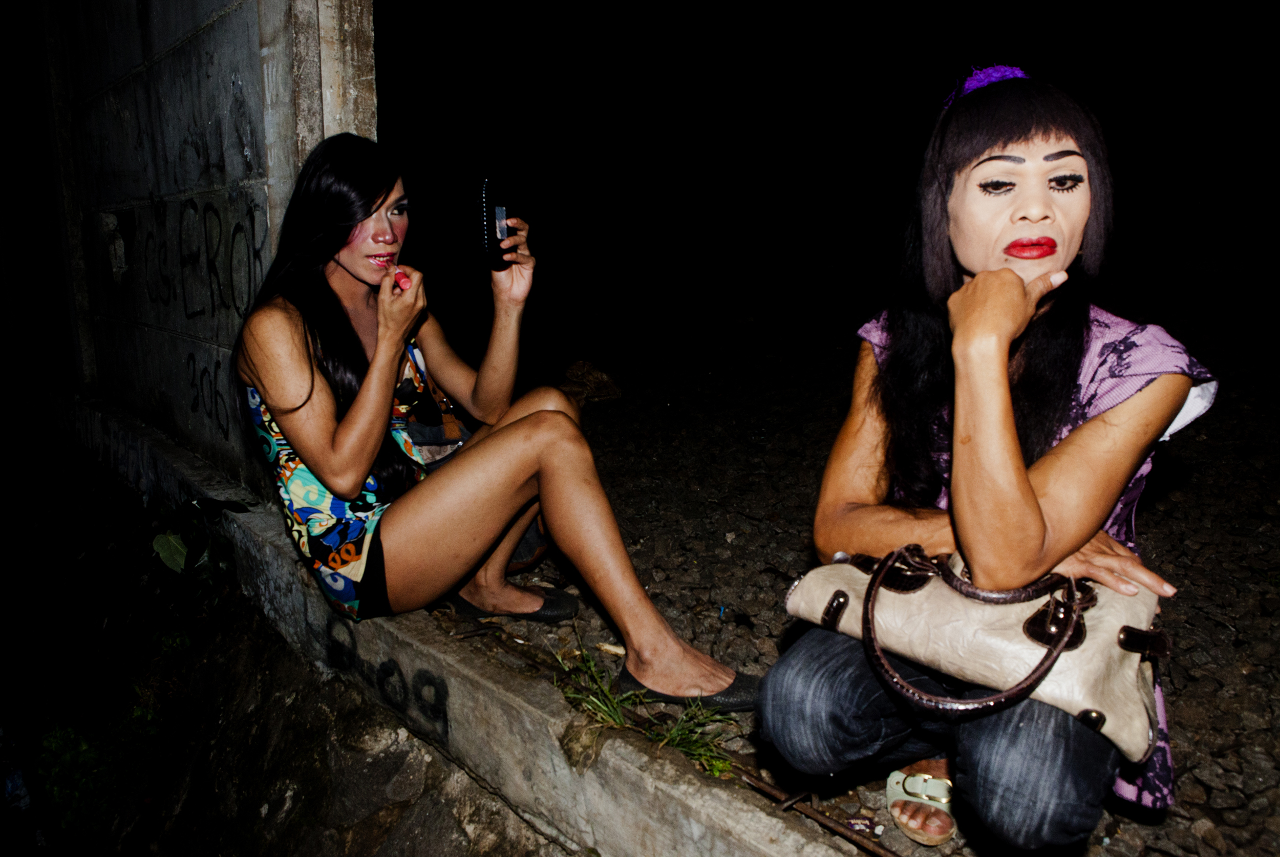 There are common threads in the lives of many warias. Sex work is one, mainly because there aren't many job opportunities for warias who live openly. They are seen as sex objects by men, or as a spectacle at nightclubs. They are often the victims of sexual violence and homicide.   Caption: Miska, right, and a friend sit on the edge of the train tracks waiting for clients. Miska said she is physically attacked and raped while working at least two times a year, if not more.