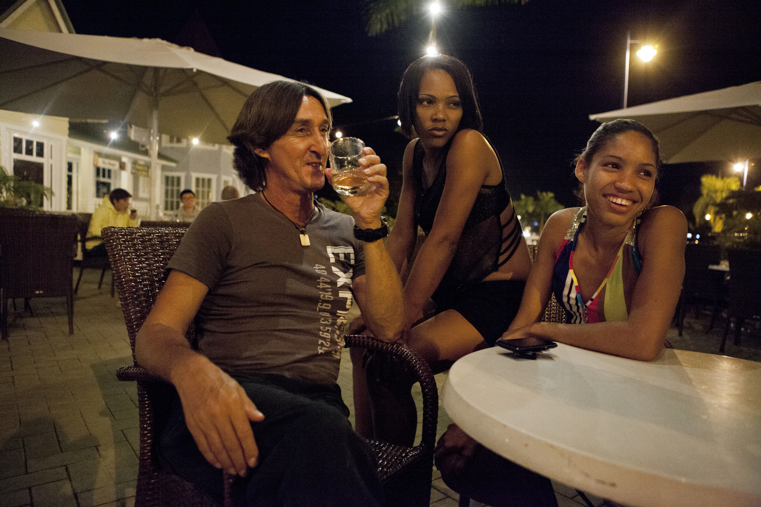 "Berenise and Chabeli have drinks with a client at a restaurant in the tourist waterfront. The Canadian tourist is a regular client for Chabeli and he believes that she is 21, not 15. When asked why he likes come to Samaná for the winter, he said, ""This place is a paradise for men. These Dominican women just love to have sex."""