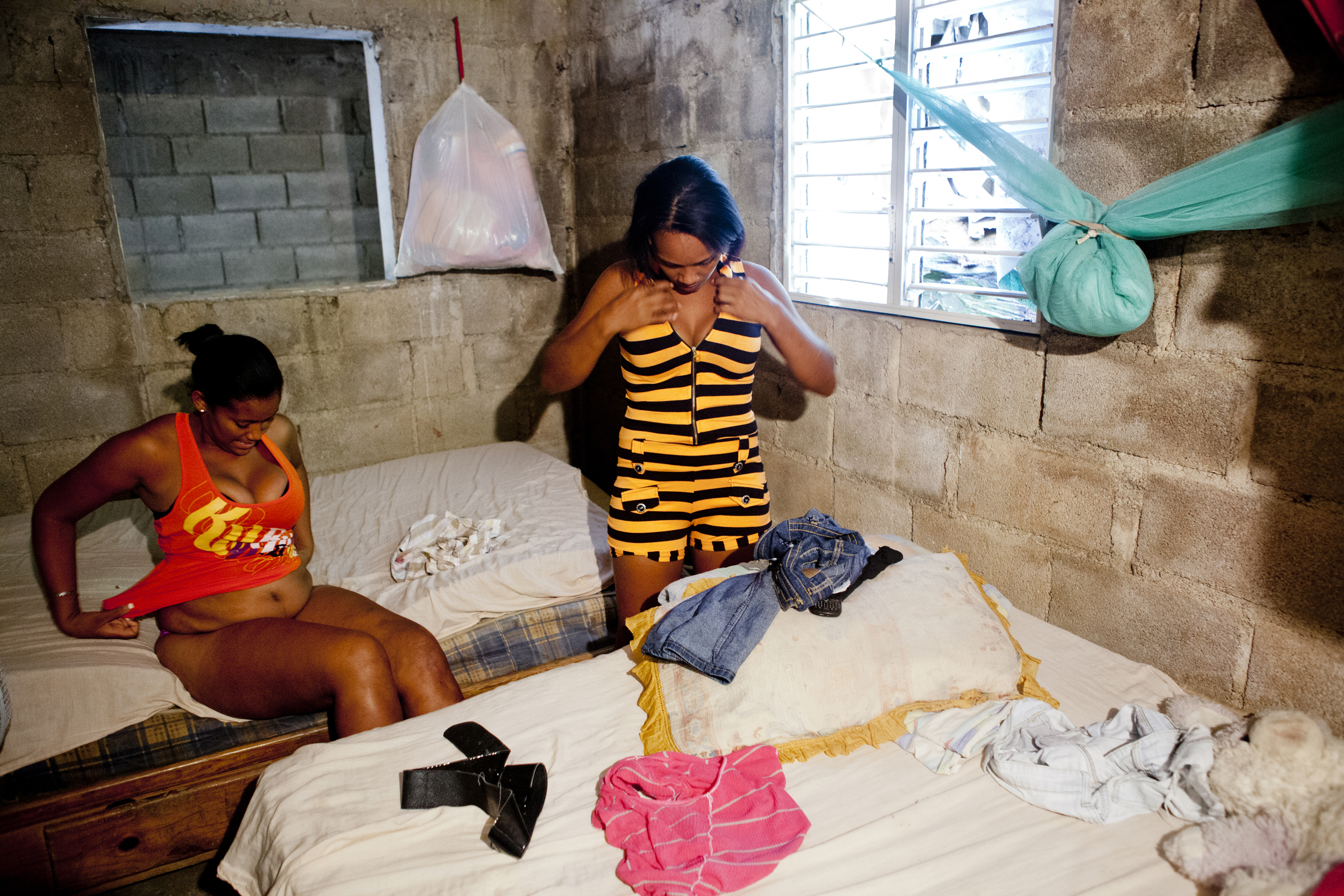 Yoleidi and Berenise get dressed to go out and work. The girls usually make $20-50 per client, and at most have two clients per day.