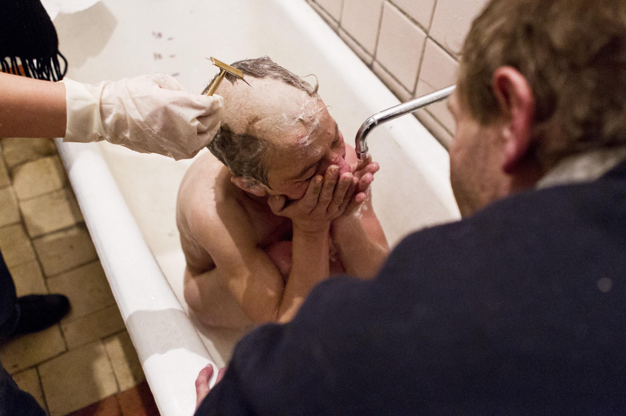 Natasha cries as Artur and a nurse wash and shave heratBishkek Hospital Number Four.