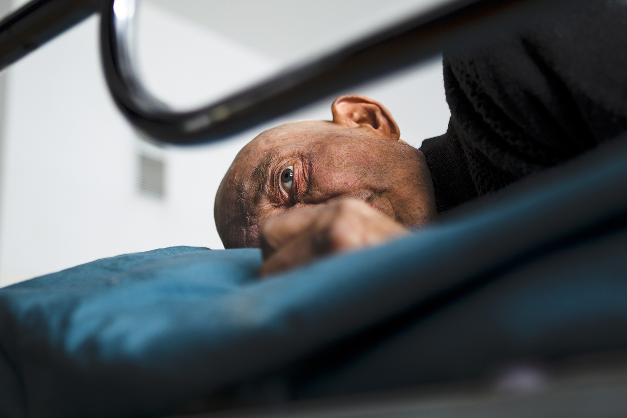 Alexander Vladimirovich lays on his bed in the overcrowded homeless room at Bishkek Hospital Number Four.
