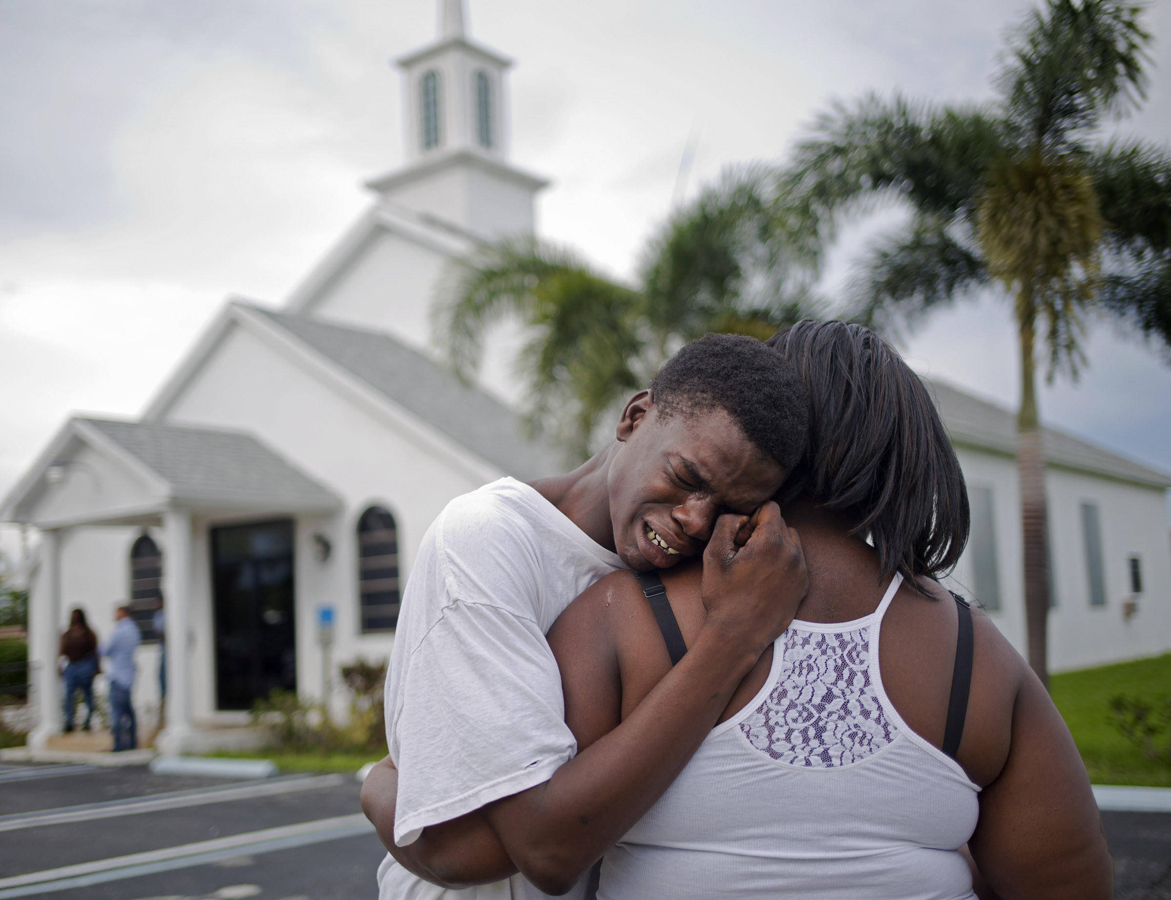 Lawerence Alston, 17, cries on the shoulder of a friend during the wake of his best friend Johnny Taylor Davis Jr. who was killed in a drive-by shooting in his North West Palm Beach neighborhood.  Davis' neighborhood, which is just a few miles away from Trump's winter home Mar-a-Lago, was ravaged by gun violence over the summer of 2015. Overall, ten people were killed at 28 were wounded.