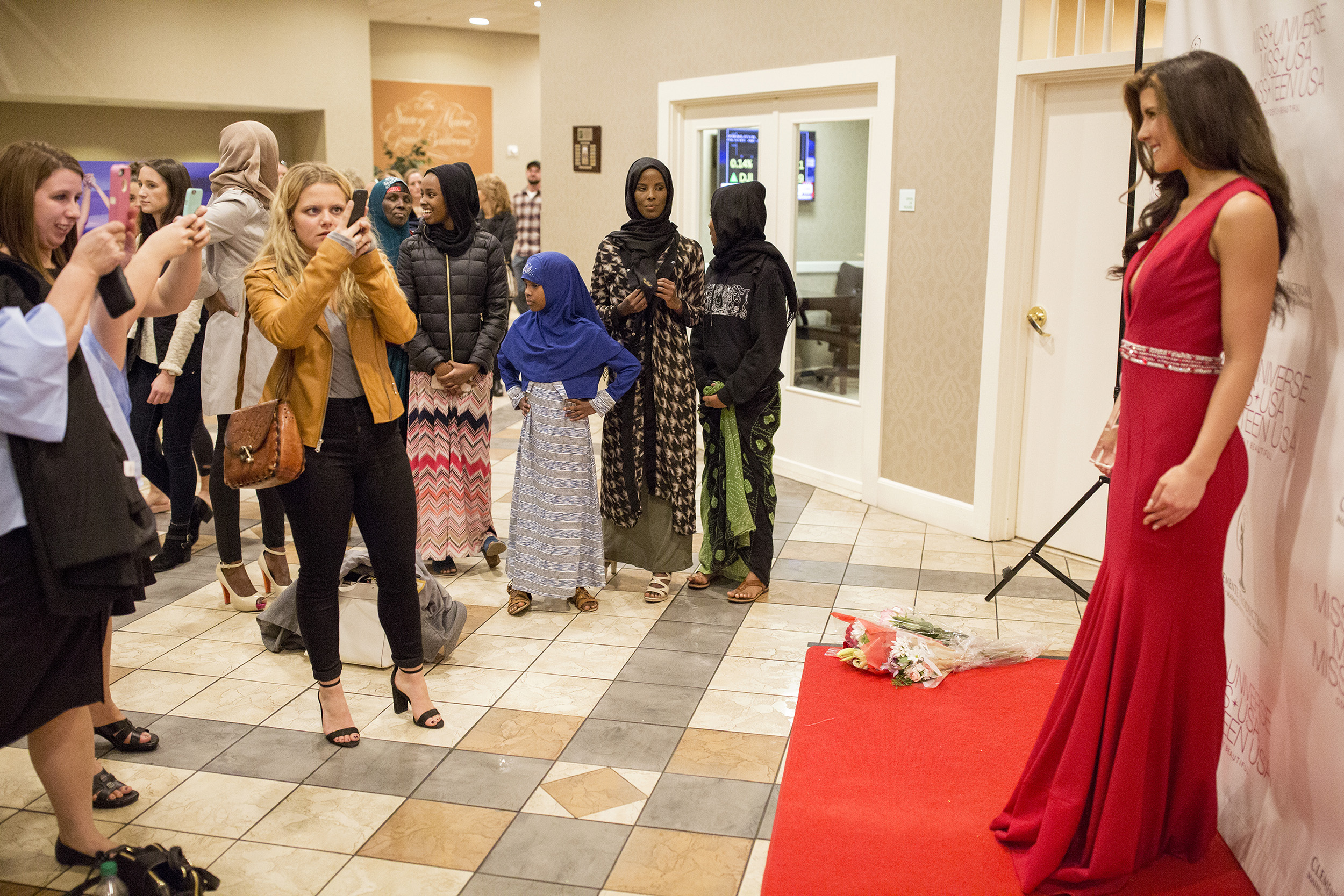 "Ahmed and her family watch as Ahmed's roommate Kaitlyn Beckwith, who was second runner up, has her photo taken in front of the Miss Maine USA sign.  ""I would love to see a Muslim girl win the pageant in the state of Maine. To go out there and say: 'This is who I am. I'm not going to change who I am, but I belong here. I have the same dreams like all of these girls, but I want to dress modest and respect my culture and religion,'"" Ahmed said. ""I want to see that day happen."""