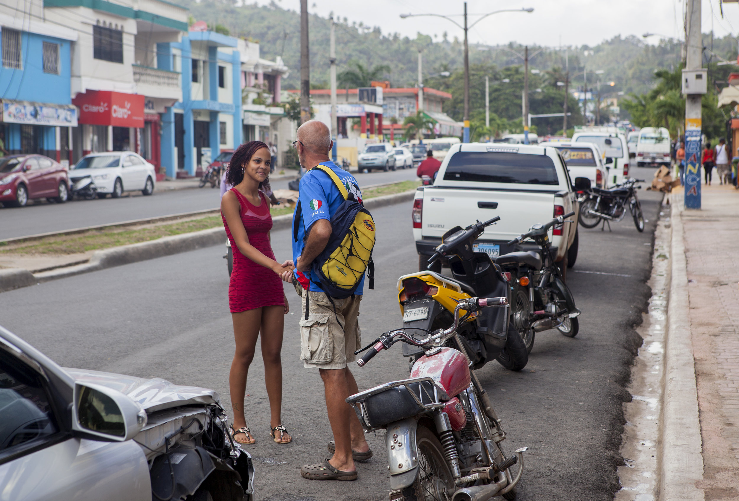 An Italian tourist greets a sex worker on the street in Samaná. Although Samaná isn't the most well-known sex tourism town in the Dominican Republic, Berenise, Yoleidi and Chabeli are just a few of the many sex workers in town.