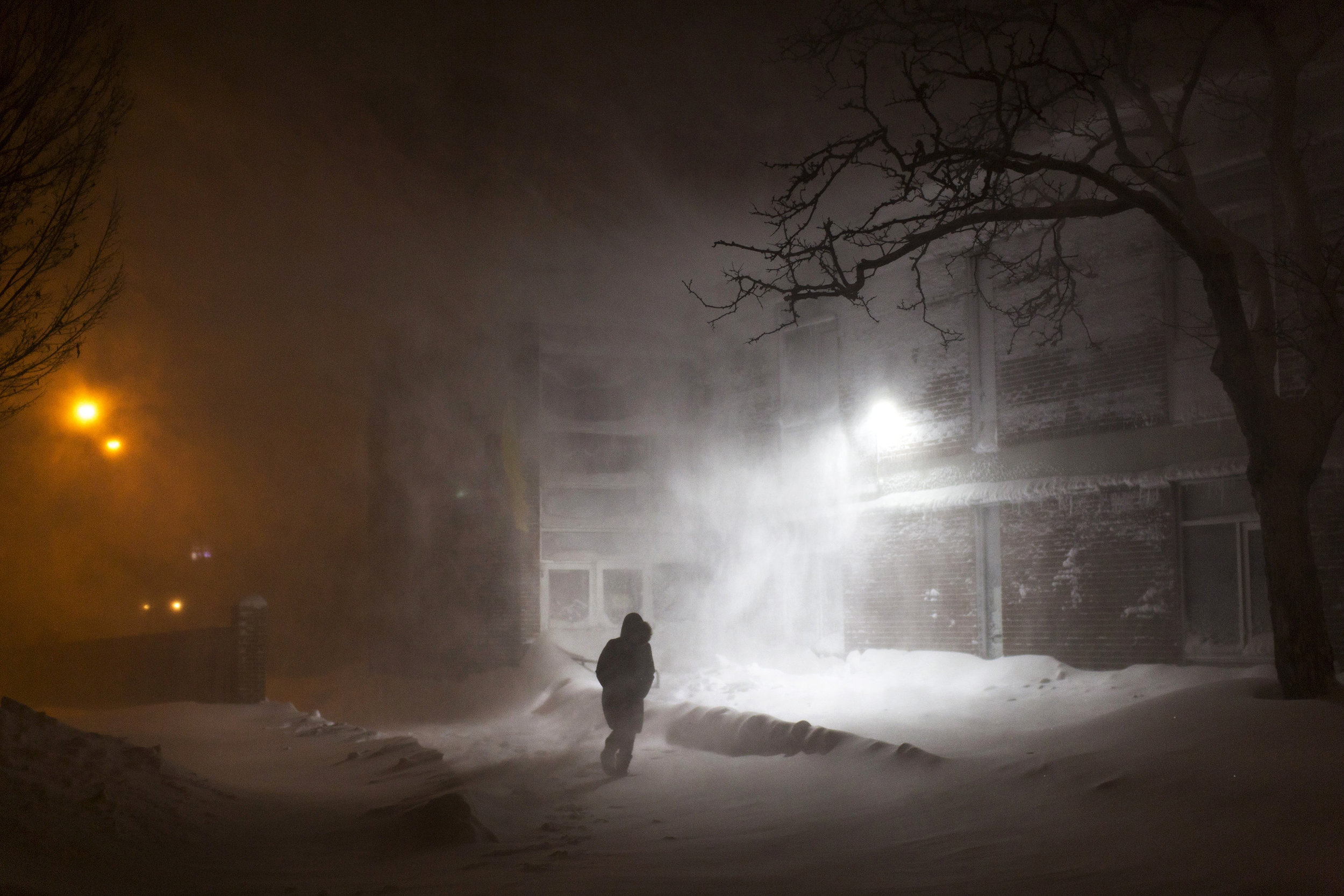 A woman walks through a park in Portland, Maine during a strong winter nor'easter.