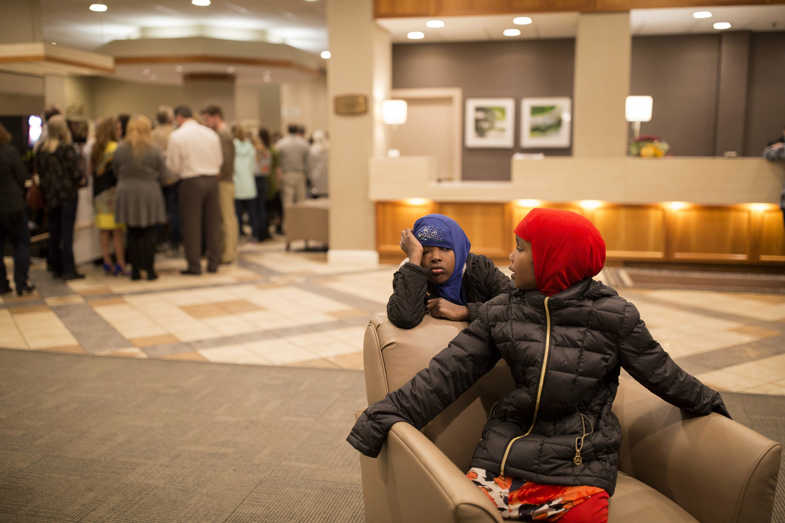 Hamdia's nieces, from left, Jamila, 7, and Zaytuun, 5, wait in the lobby of the Holiday Inn for the pageant to start. Hamdia's family, her mother sister and three nieces, paid the money to come and support her for both nights.
