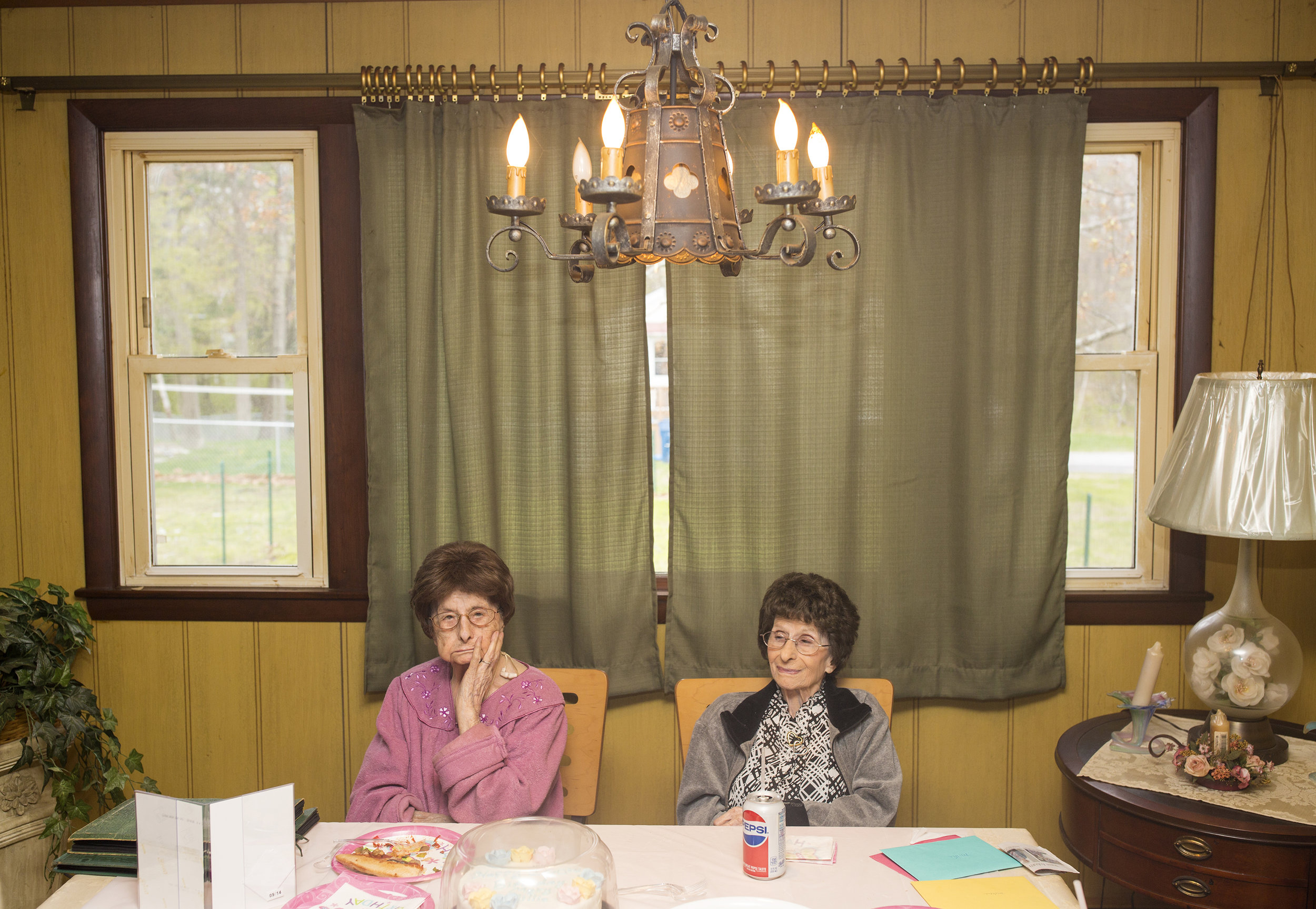 """Identical twins Mary McCarthy, left, and Amelia """"Millie"""" Lane celebrate their 100th birthday with their children and grandchildren at Mary's home in Portland, Maine."""