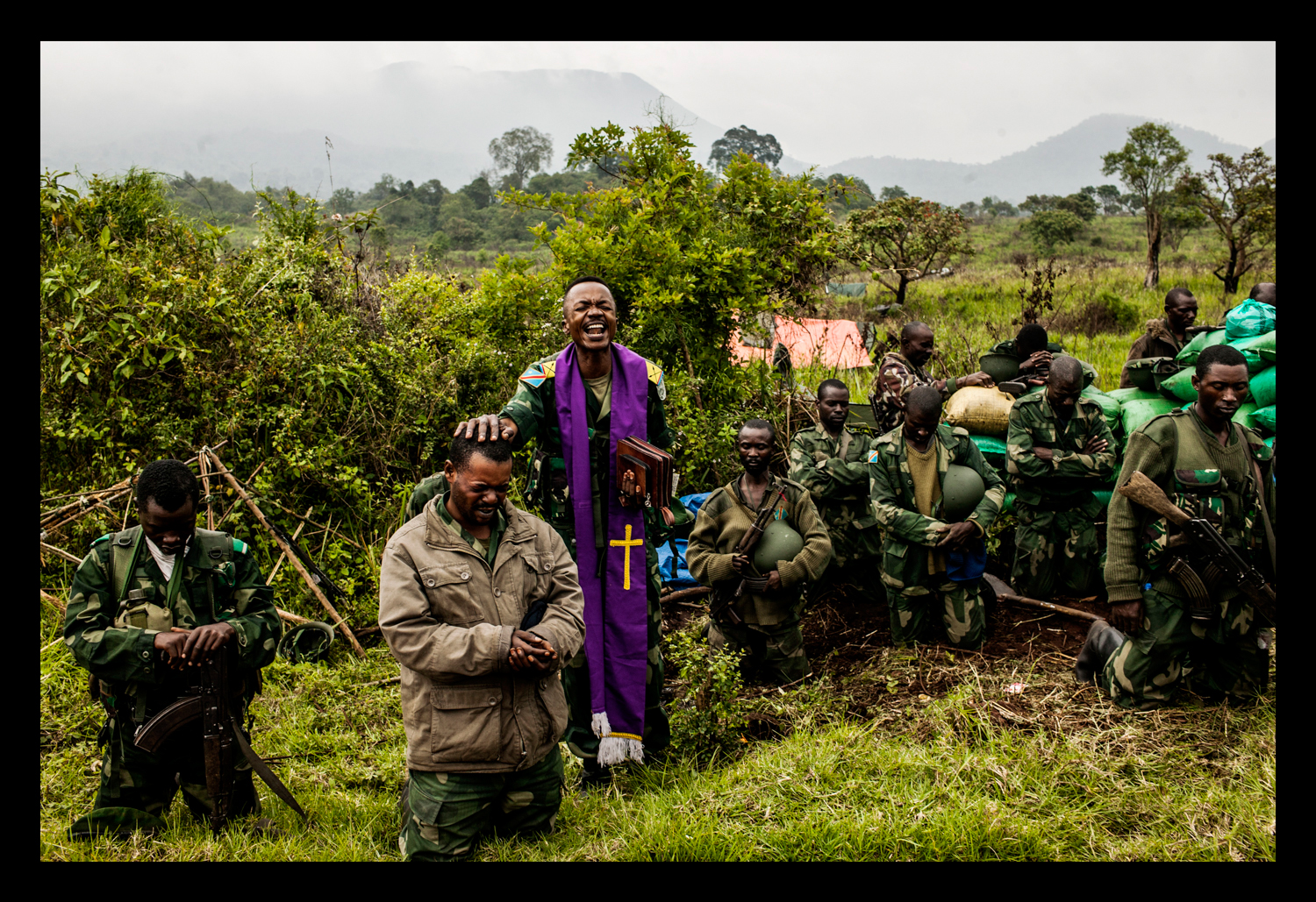 A Congolese military chaplain prays with the soldiers