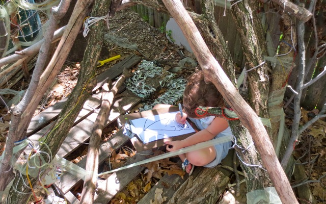 "Drawing her play in the fairy nature den. ""I like to alone-play in this den,"" she tells us."