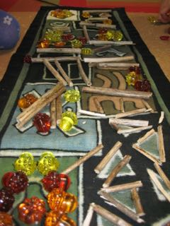 Plastic acorns, pumpkins, and cut day lily stalks on mud cloth.jpg