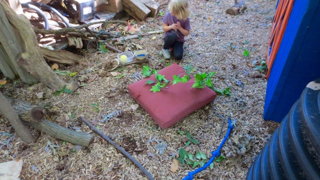 Setting up house in a completely imaginary way with walls indicated by a branch and a rope. The cushion serves as both stove and bed. The time and space to shape this play needs to be roomy and deep.