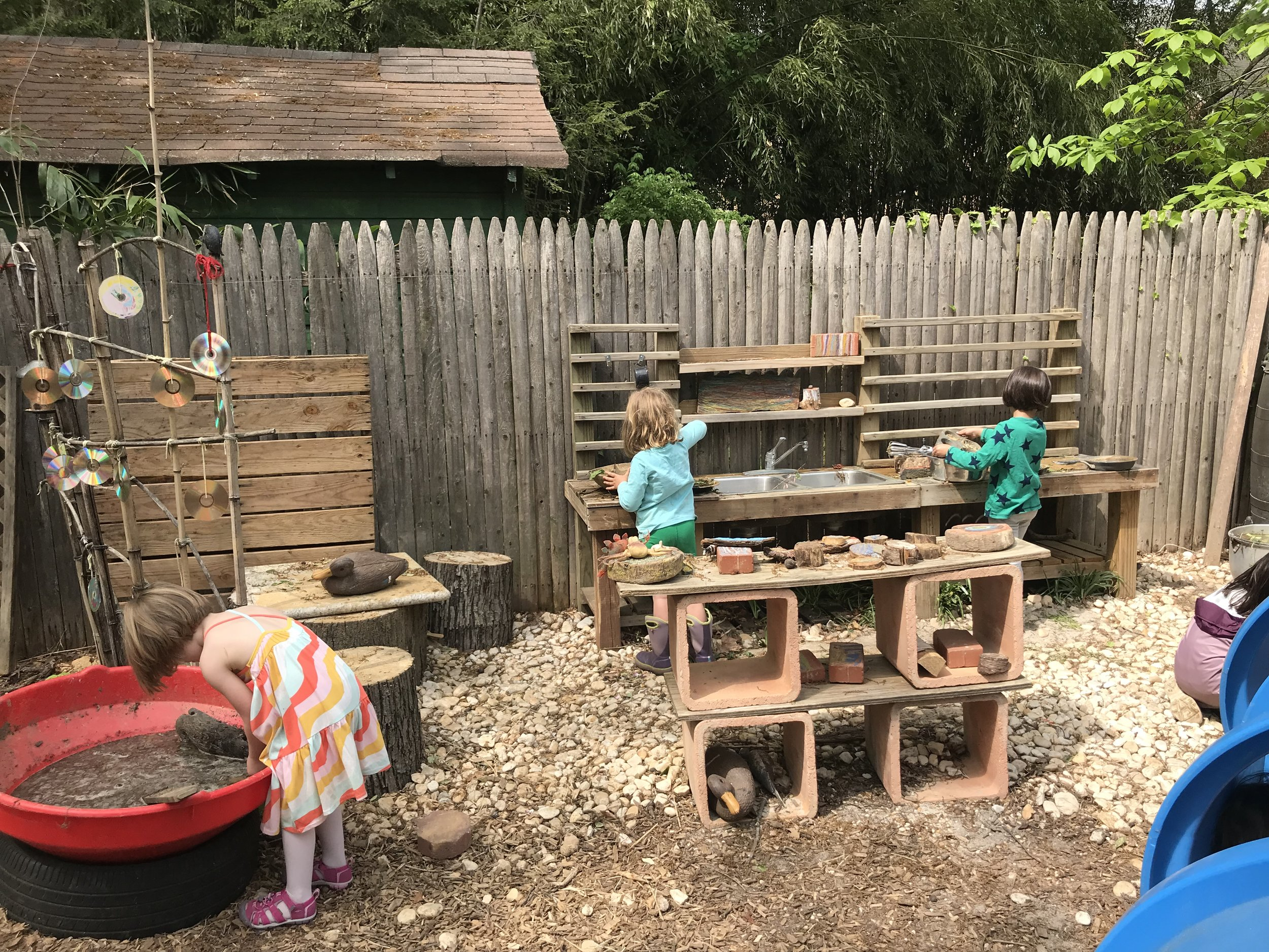 Meanwhile at the mud kitchen, things are really cooking. So much going on over here. The play is deep and wide.