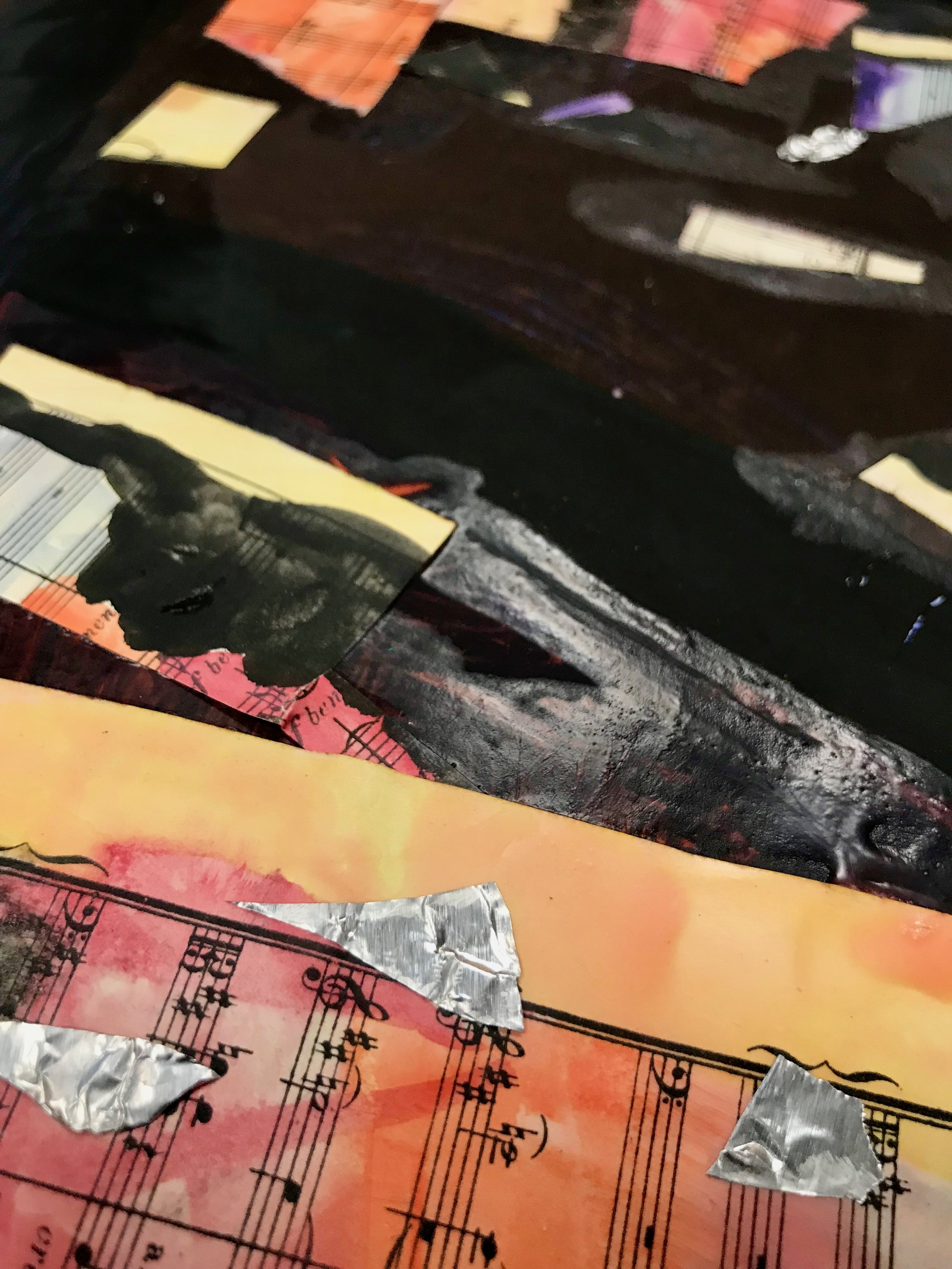 Detail from a child's work of art. The detail shows the watercolor music sheets cut into smaller rectangle/squares with tin foil embellishments along tempera lines and blocks of color.