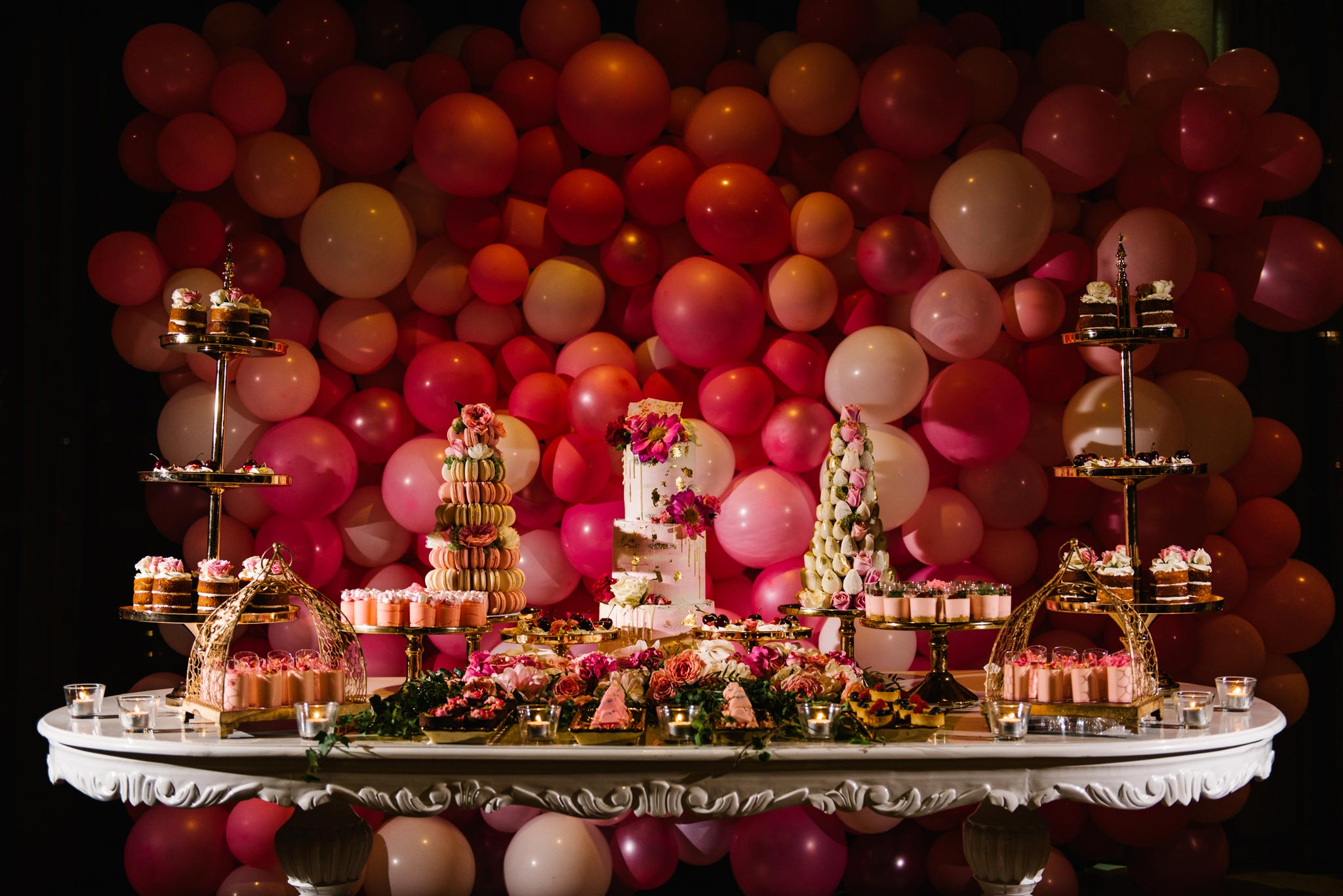 Pink christening cake table with multicolour balloon backdrop