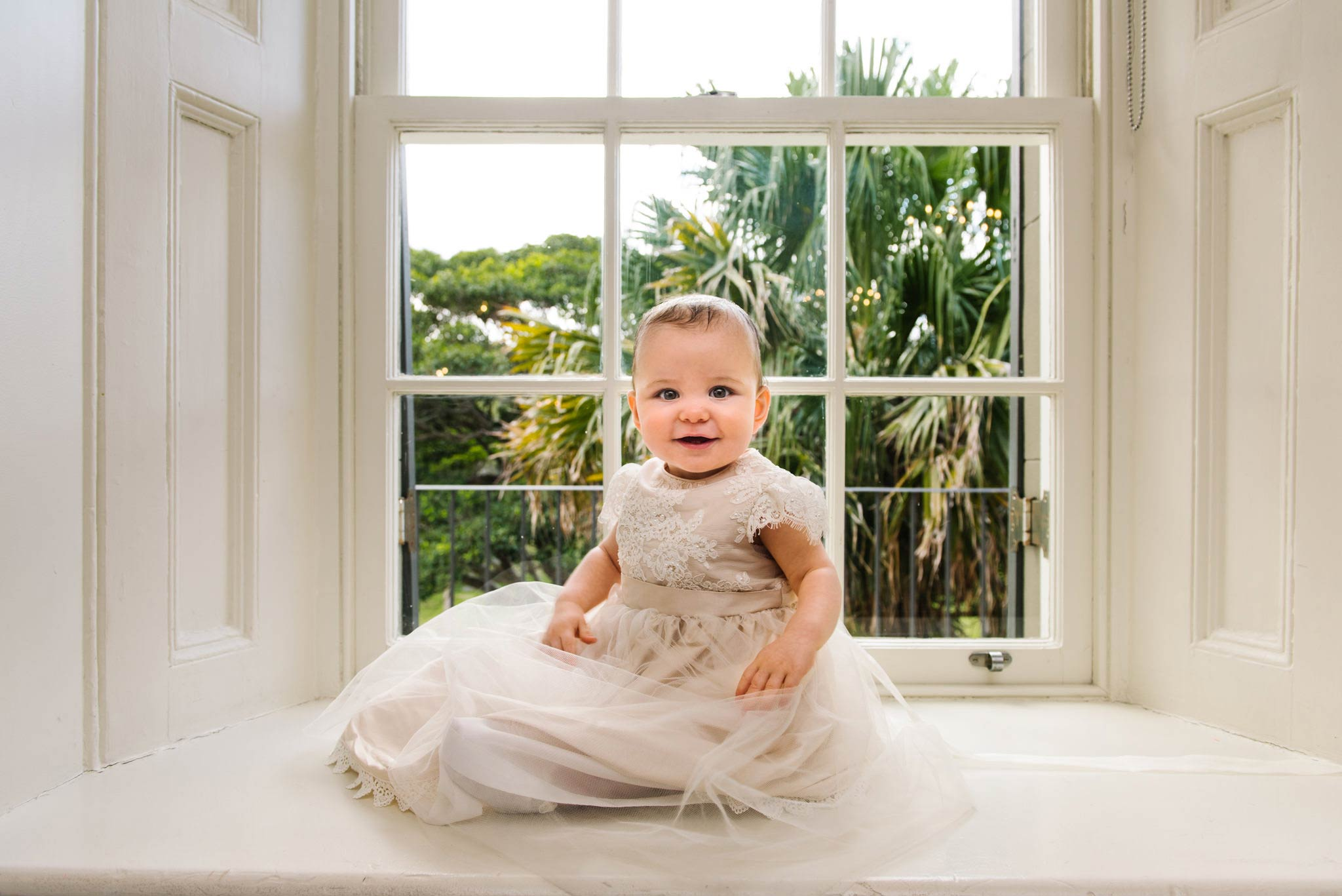 Baby in christening gown with sash windows at Dunbar House